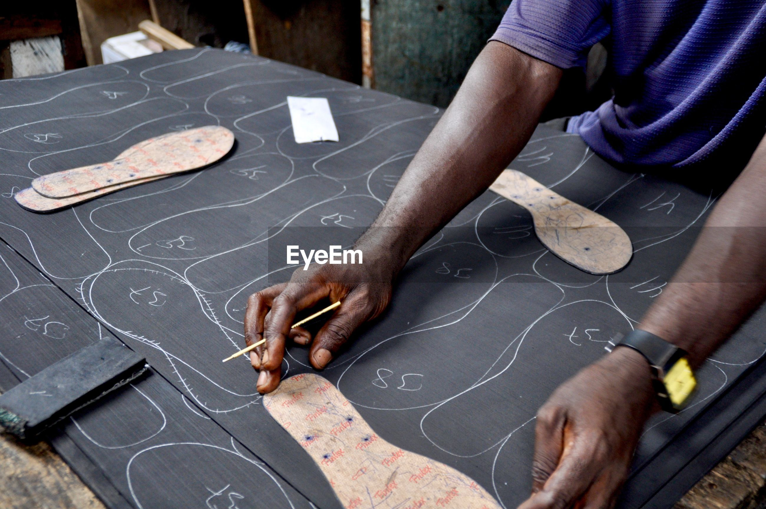 Midsection of man cutting sole