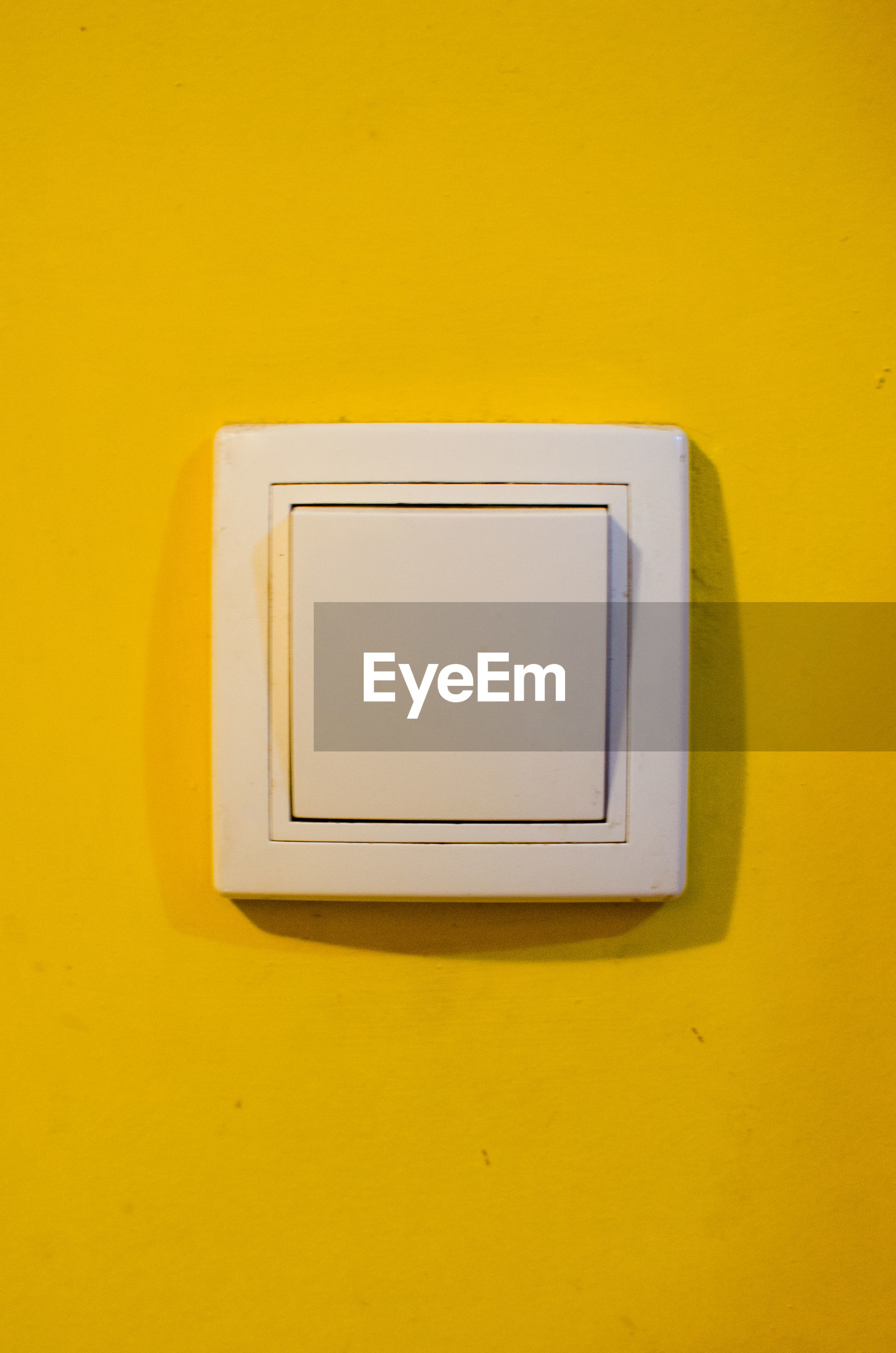 Full frame shot of light switch on yellow wall