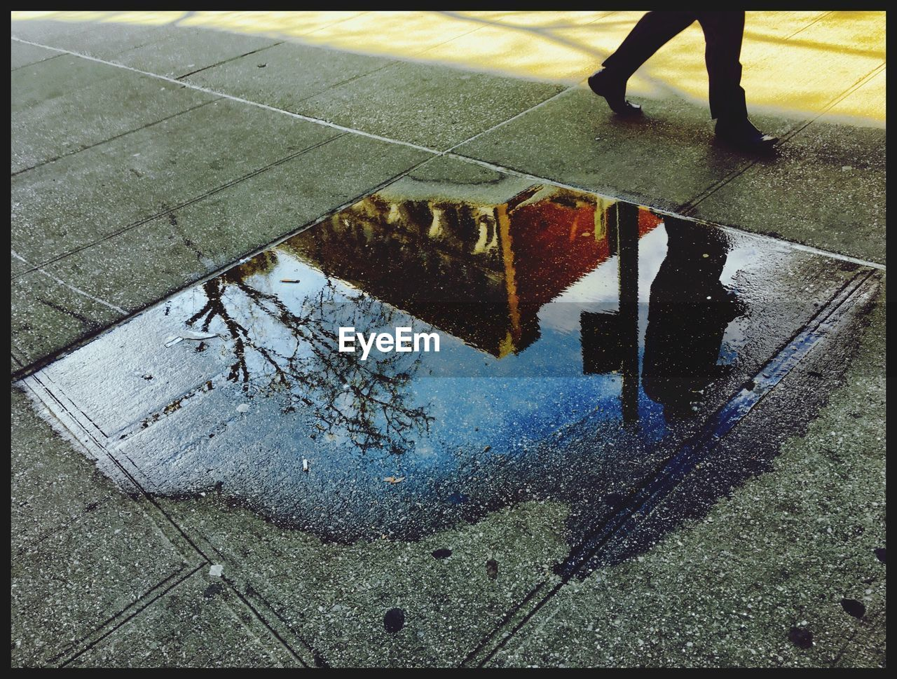 High Angle View Of Puddle With Reflection Of Person Walking On Footpath And Building
