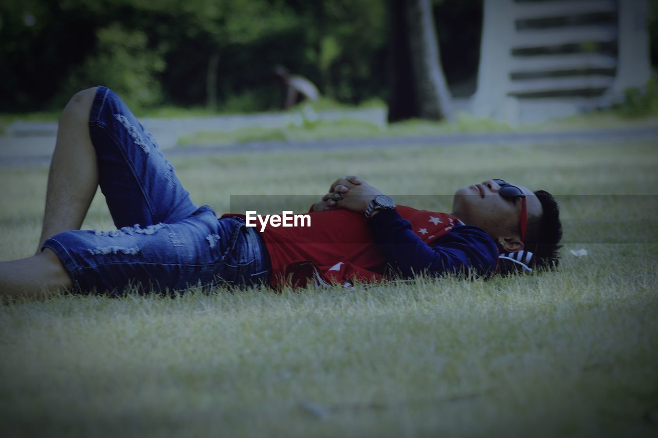 SIDE VIEW OF BOY LYING ON GRASS