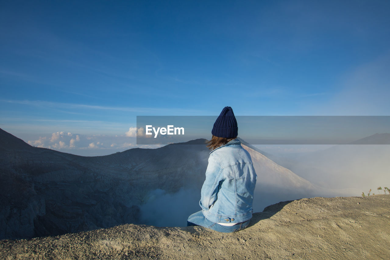 sky, one person, real people, leisure activity, lifestyles, rear view, scenics - nature, sitting, beauty in nature, nature, tranquility, tranquil scene, mountain, non-urban scene, sunlight, day, adult, clothing, women, mountain range, outdoors