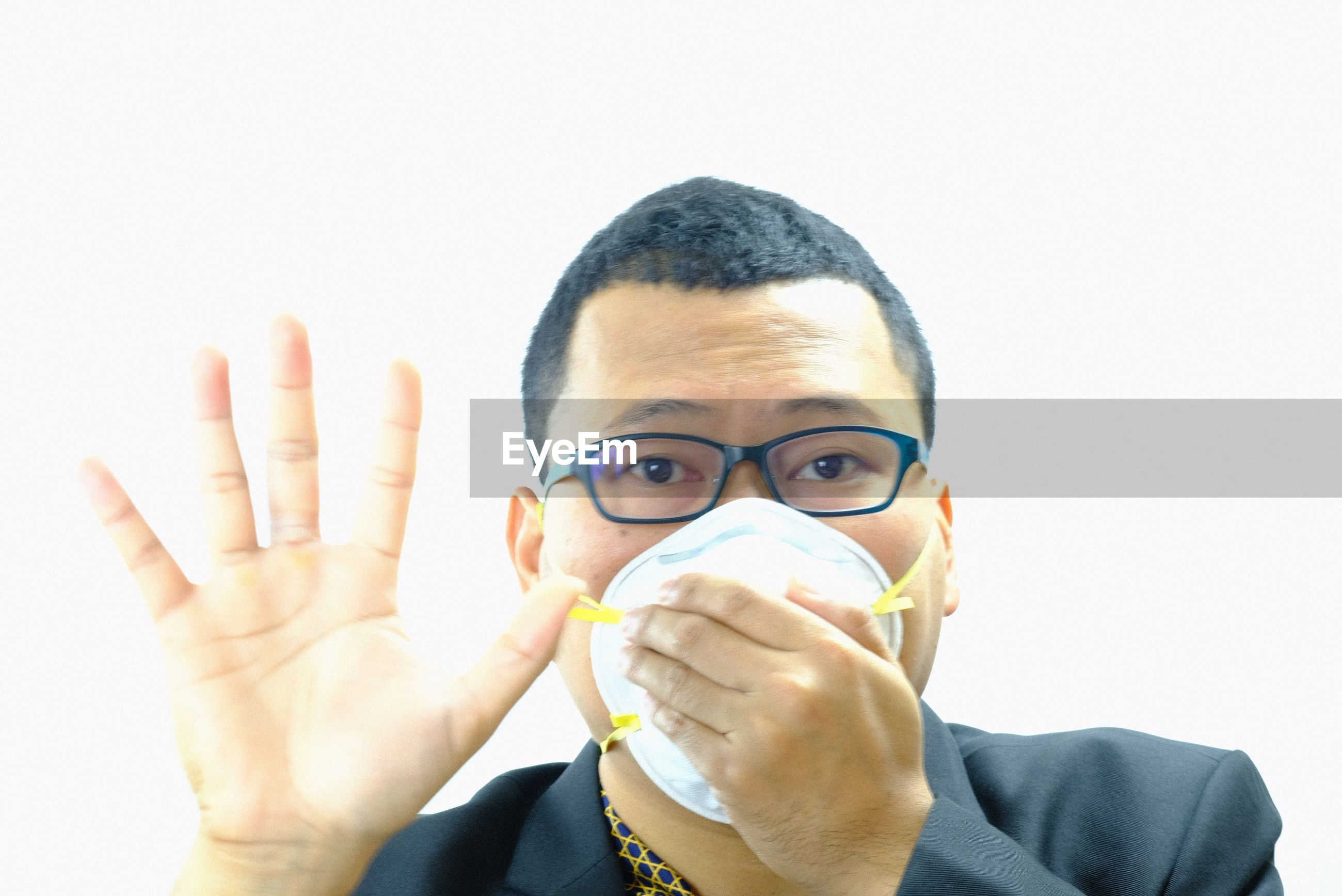 Portrait of businessman gesturing while wearing pollution mask against white background