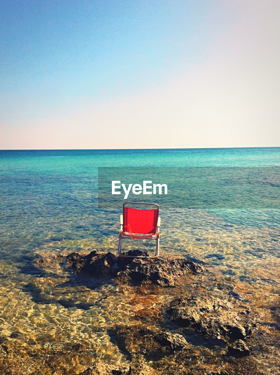 High angle view of chair on rock in sea against sky