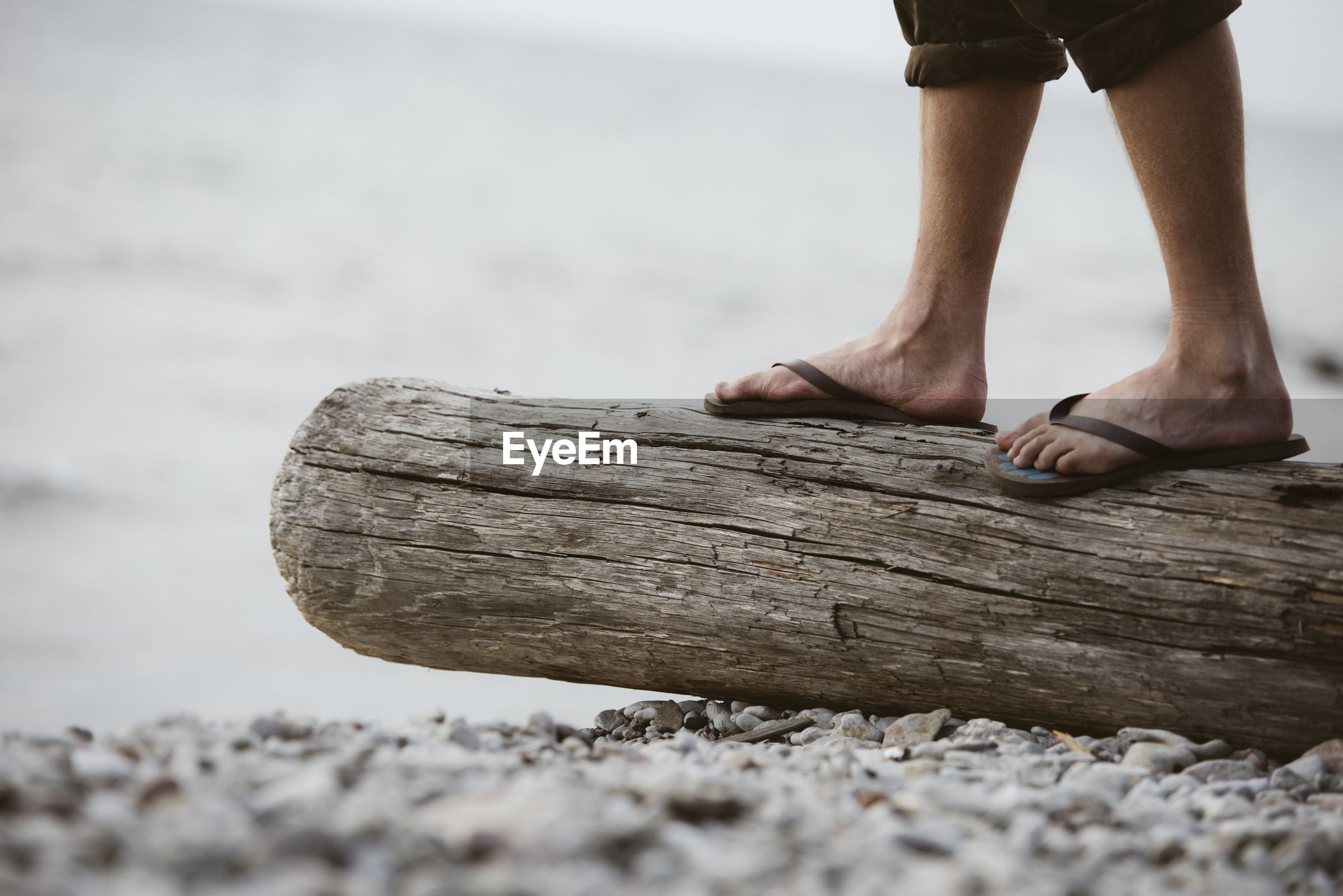 LOW SECTION OF PERSON STANDING ON WOODEN POST