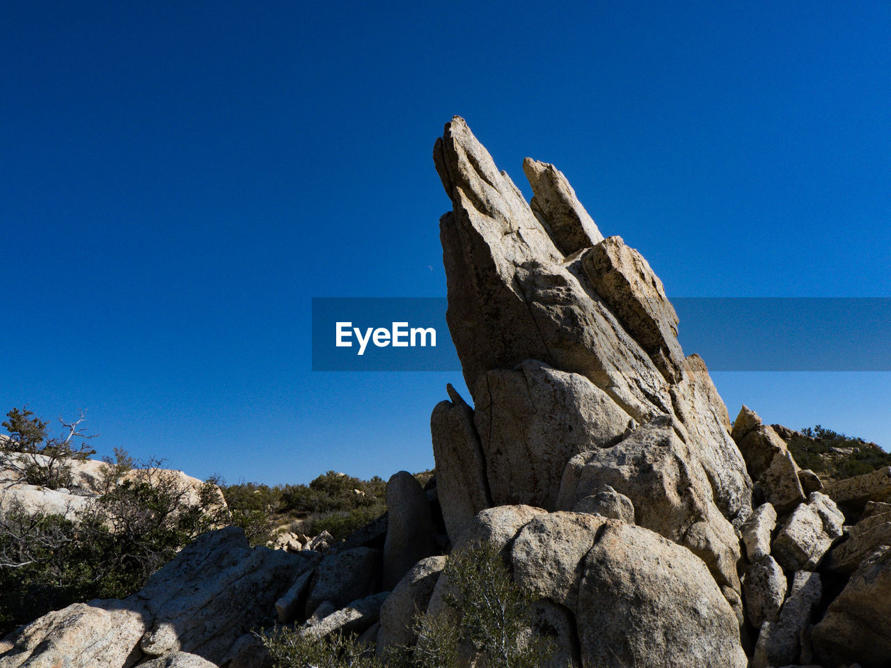 rock, solid, rock - object, sky, blue, clear sky, rock formation, nature, low angle view, copy space, day, tranquility, no people, sunlight, beauty in nature, tranquil scene, rough, scenics - nature, mountain, textured, outdoors, eroded, mountain peak, arid climate