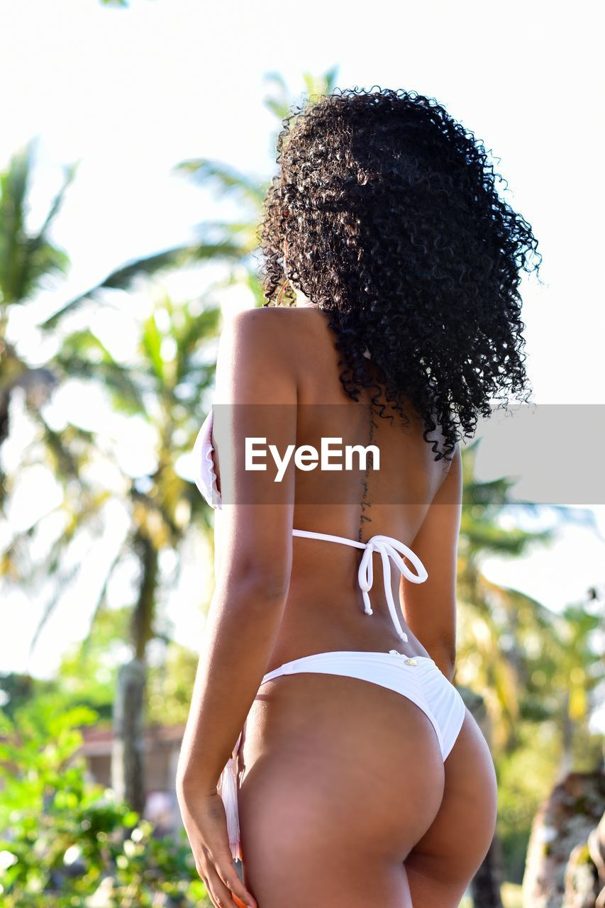 one person, hairstyle, focus on foreground, hair, women, adult, real people, young adult, swimwear, bikini, young women, curly hair, clothing, lifestyles, rear view, day, leisure activity, outdoors, beautiful woman, body part