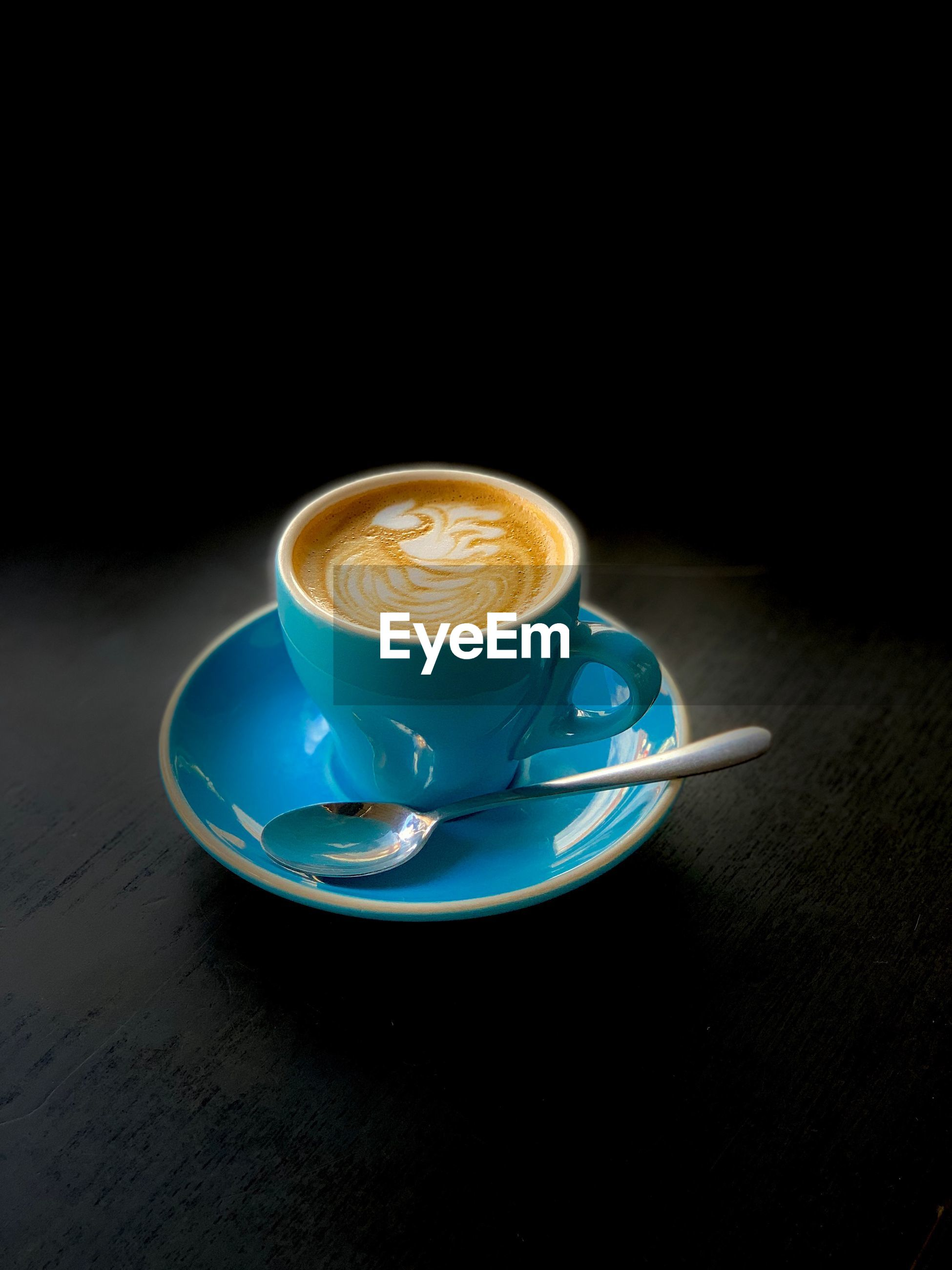 COFFEE CUP ON TABLE AGAINST BLURRED BACKGROUND