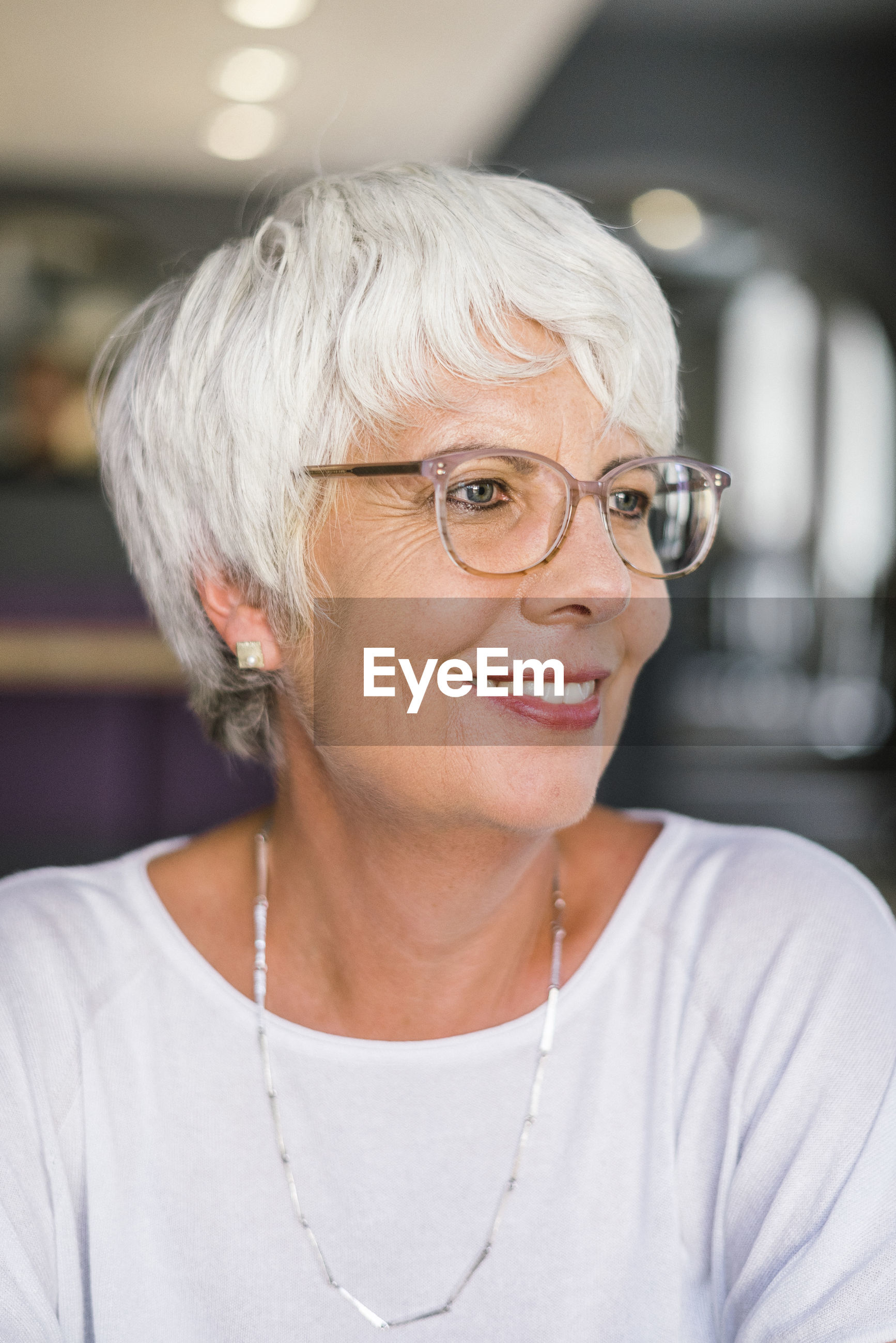 Close-up of smiling woman looking away in cafe