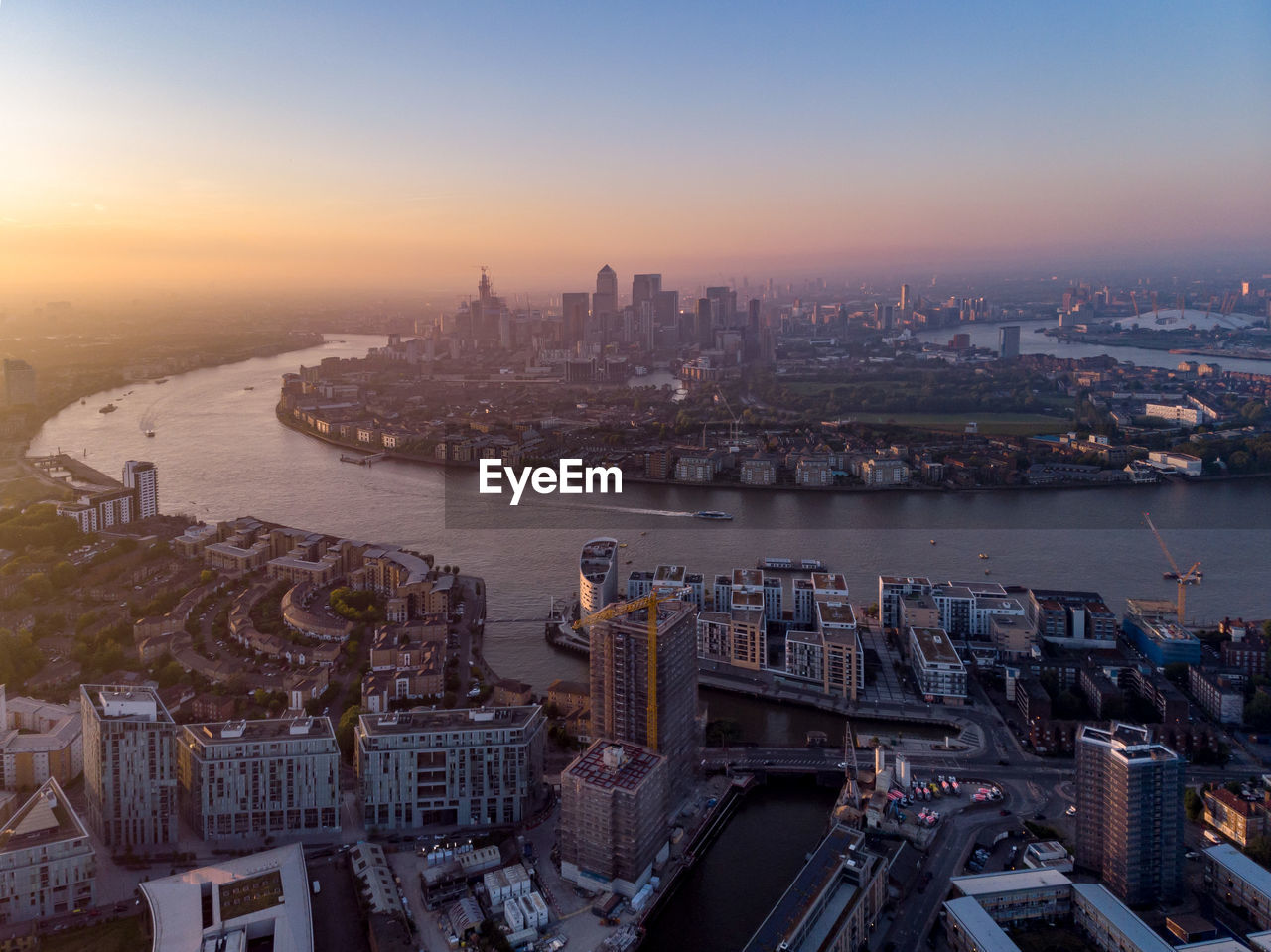 Aerial view of buildings by river against sky in city during sunset