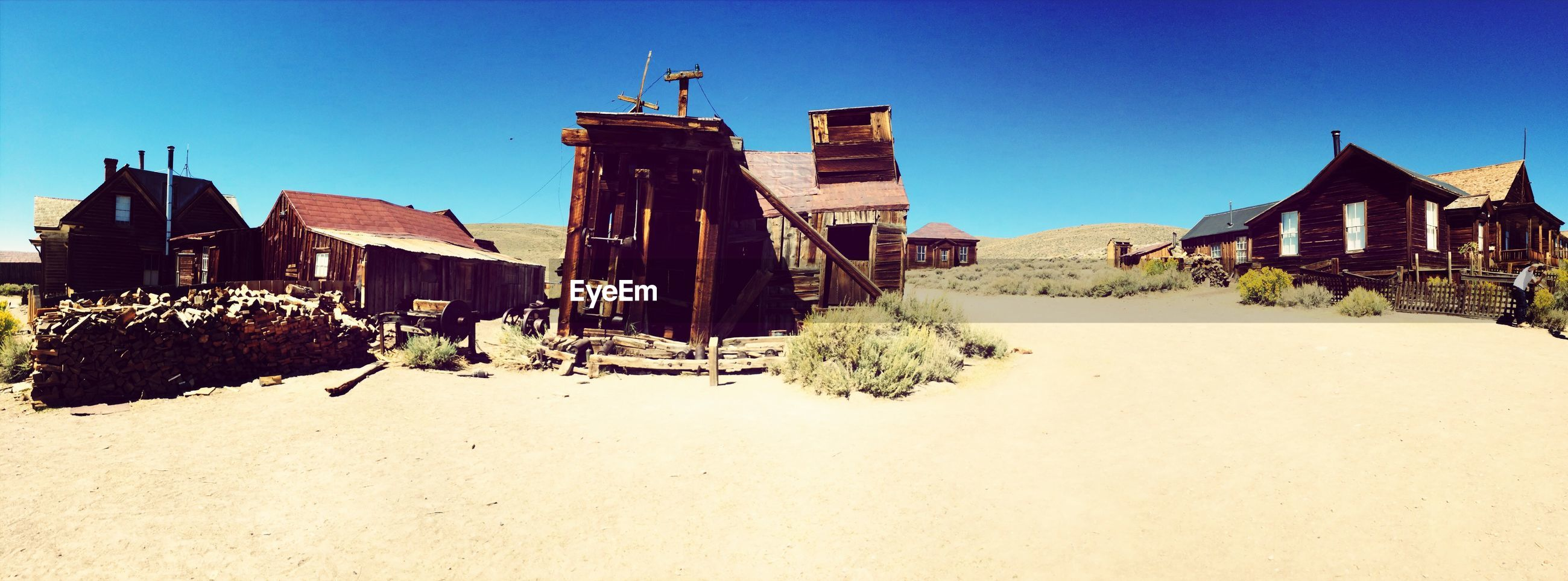 building exterior, architecture, built structure, clear sky, house, sunlight, blue, residential structure, old, shadow, day, residential building, sky, outdoors, abandoned, damaged, no people, sunny, incidental people, sand