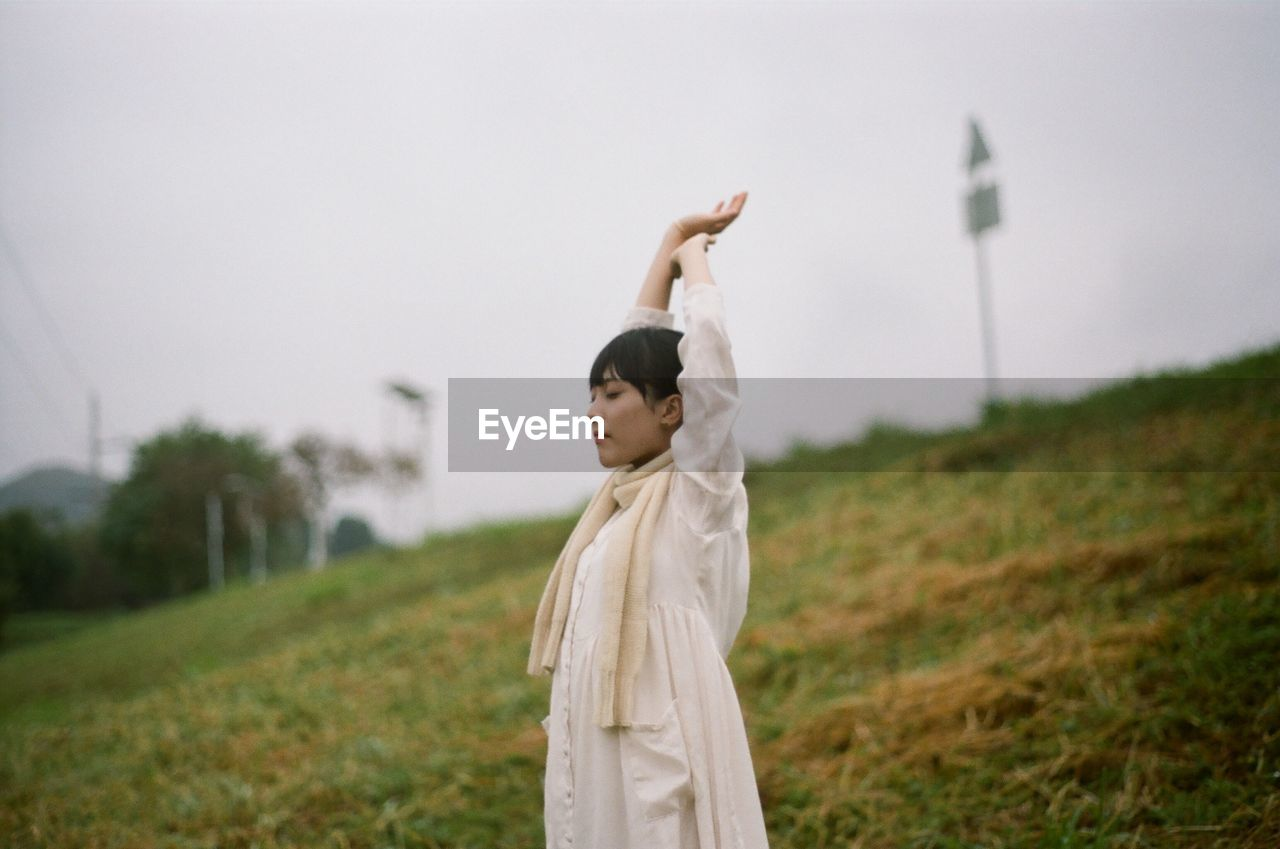 Woman Stretching On Grassy Field