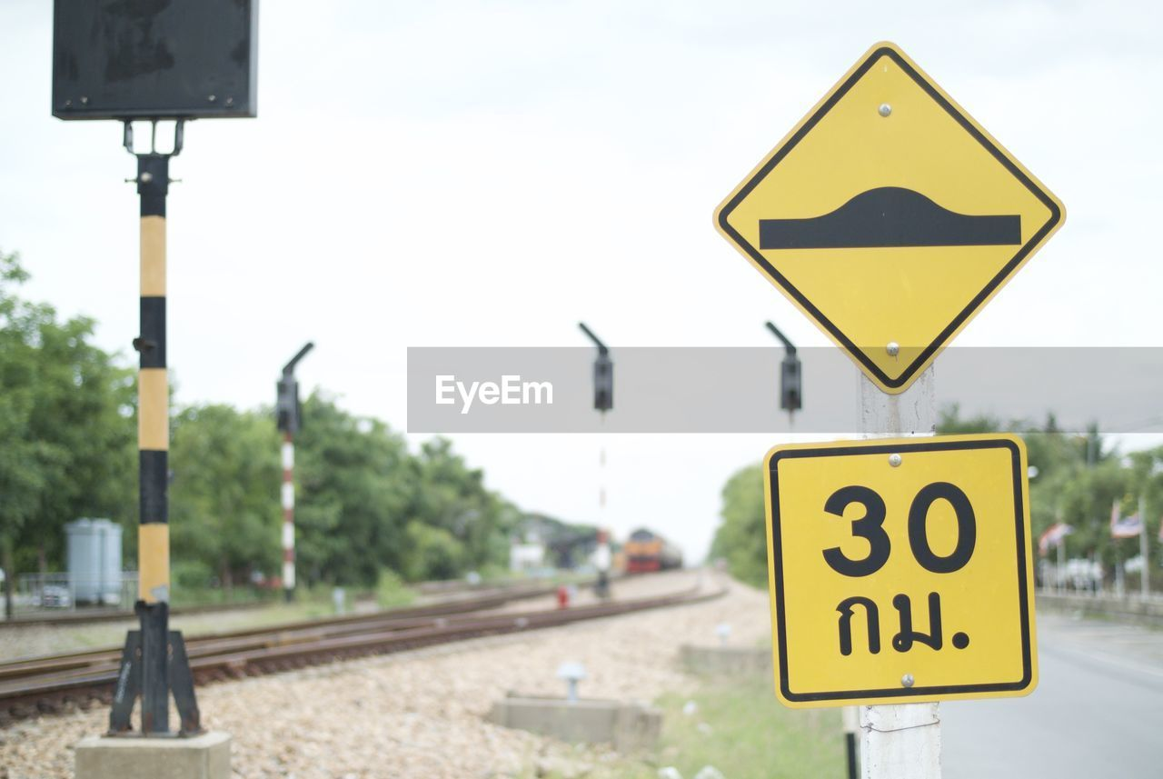 Close-up of speed bump sign by railroad track against sky