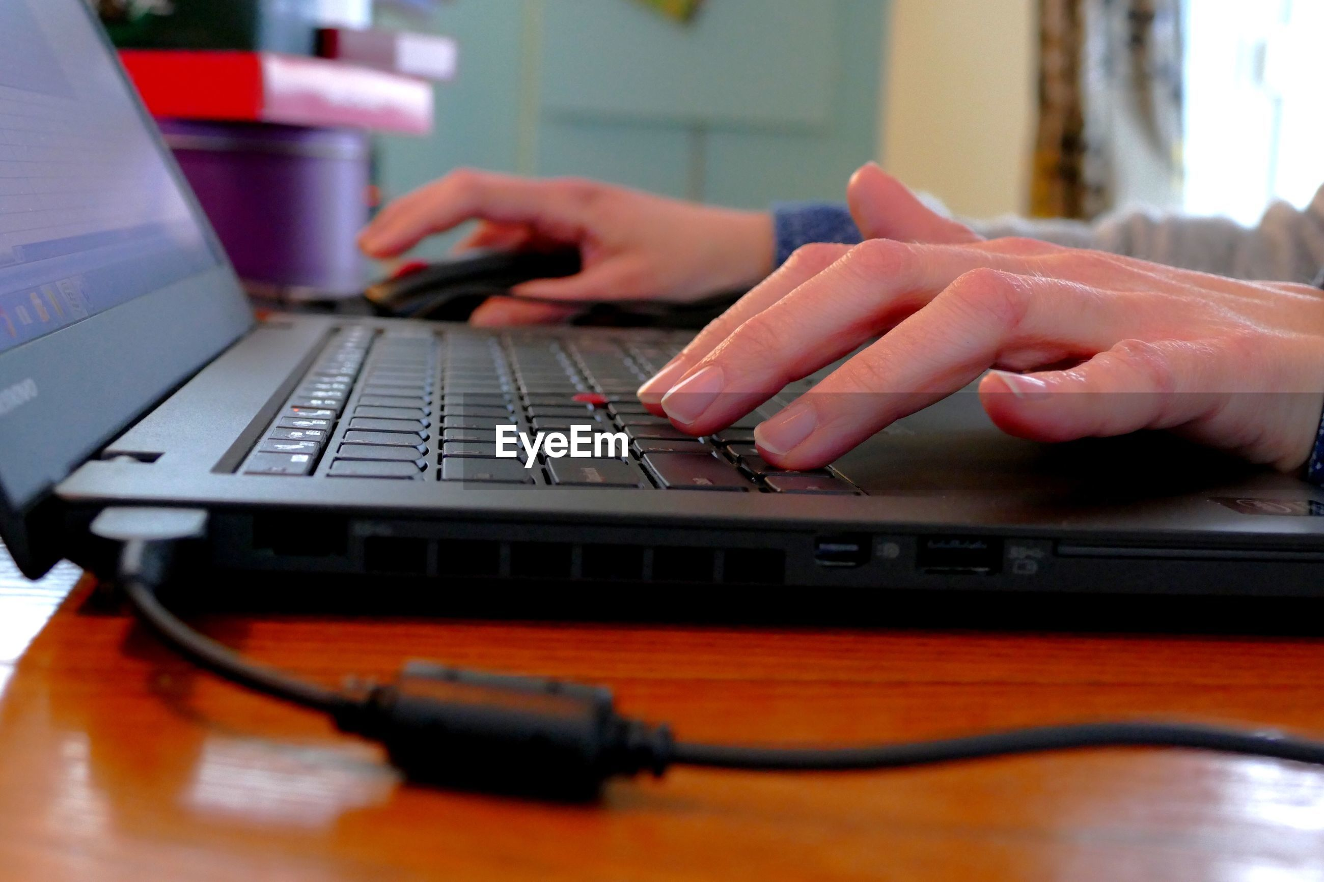 Cropped hands using laptop at table