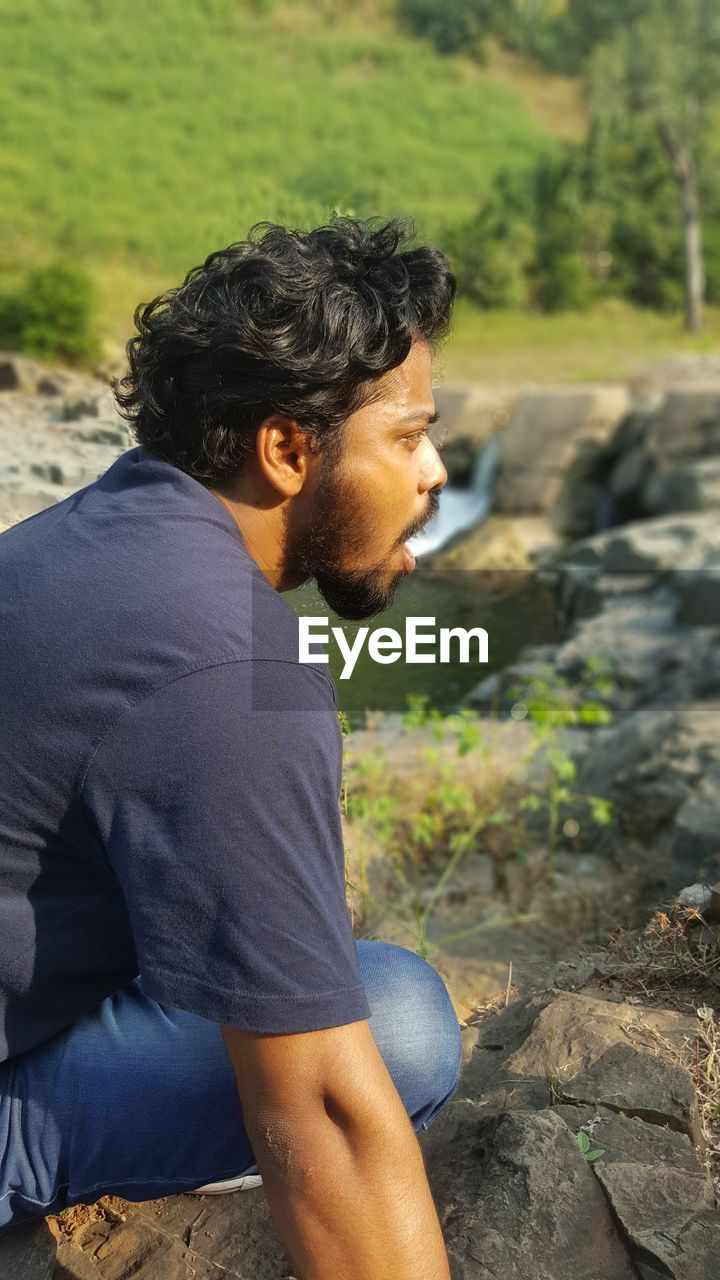side view, real people, one person, lifestyles, young men, casual clothing, focus on foreground, leisure activity, rock, rock - object, three quarter length, solid, young adult, day, sitting, land, nature, men, looking, outdoors, hairstyle, contemplation