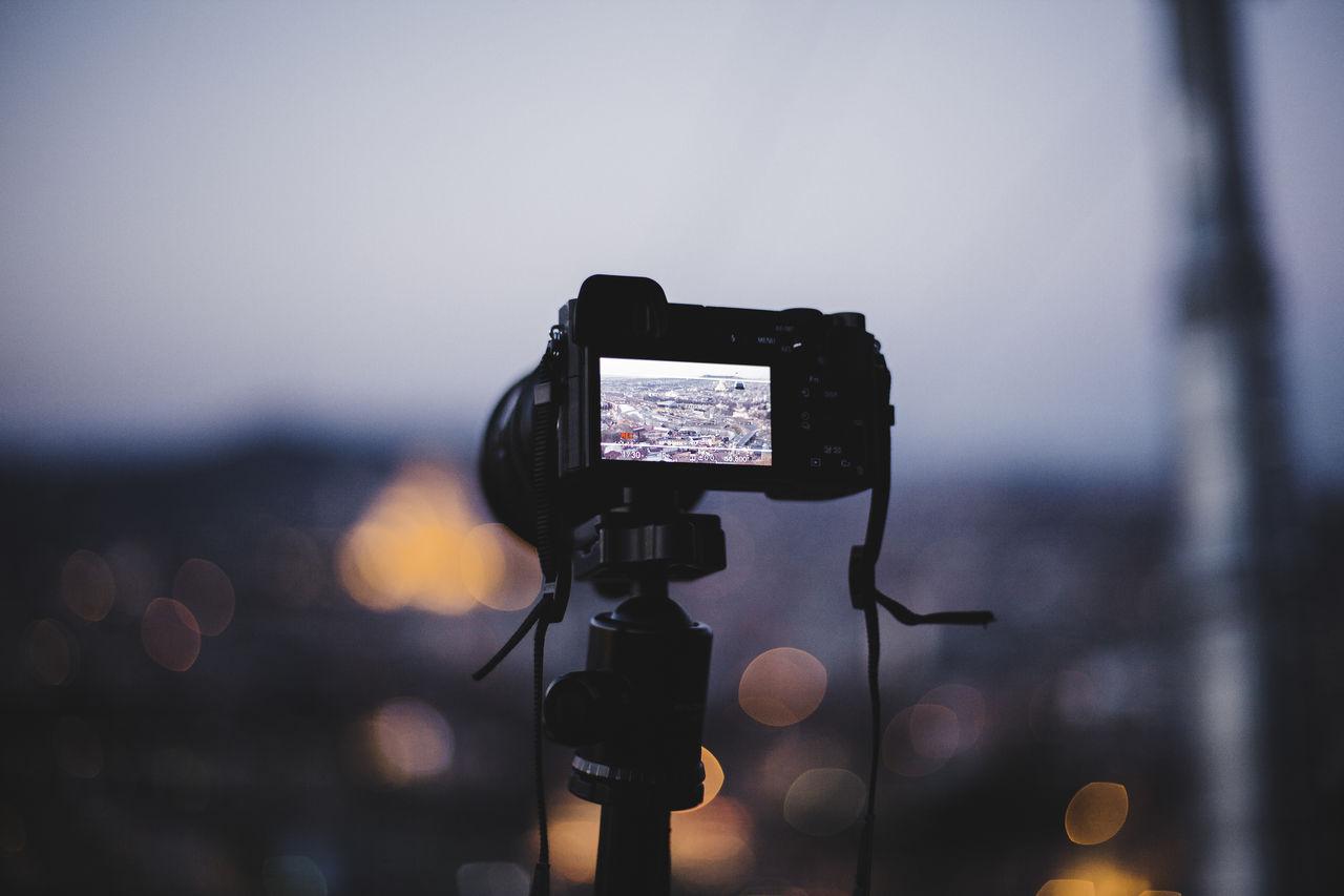Close-Up Of Digital Camera Against Sky At Dusk