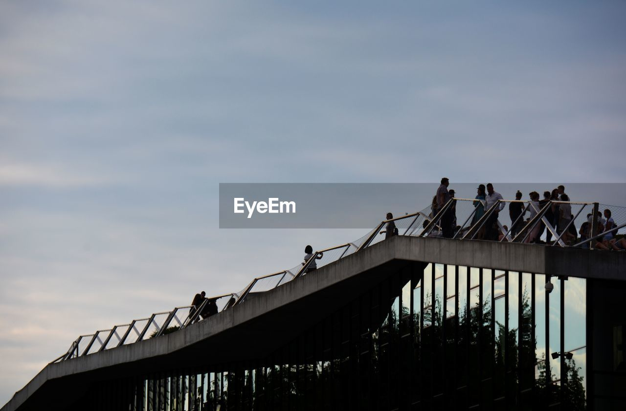 sky, architecture, built structure, group of people, bridge, low angle view, bridge - man made structure, cloud - sky, connection, railing, nature, men, real people, transportation, day, women, outdoors, lifestyles, large group of people, adult