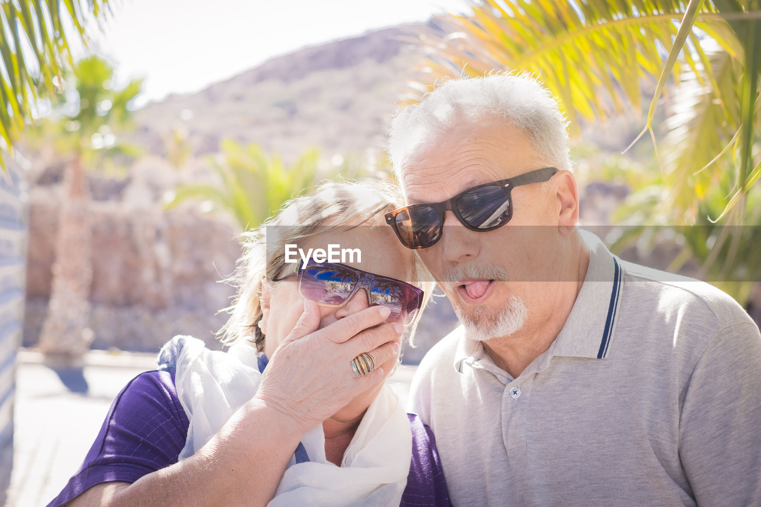 Senior couple wearing sunglasses at beach during summer