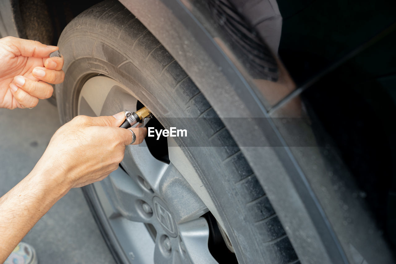 Cropped Hand Of Woman Tightening Car Wheel