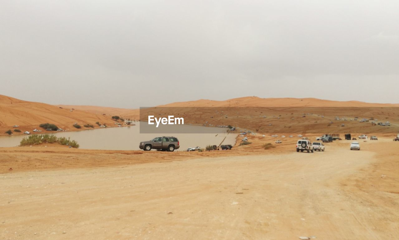landscape, environment, desert, sky, mode of transportation, transportation, scenics - nature, land, land vehicle, motor vehicle, climate, nature, day, arid climate, car, tranquil scene, non-urban scene, beauty in nature, no people, off-road vehicle, outdoors, dust
