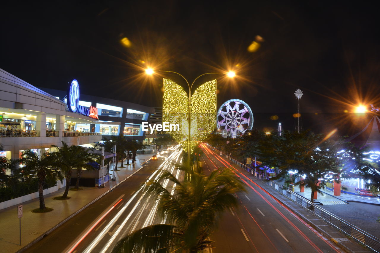 illuminated, night, motion, transportation, architecture, road, long exposure, street, blurred motion, city, built structure, street light, glowing, building exterior, light trail, mode of transportation, speed, lighting equipment, car, motor vehicle, outdoors, no people, lens flare