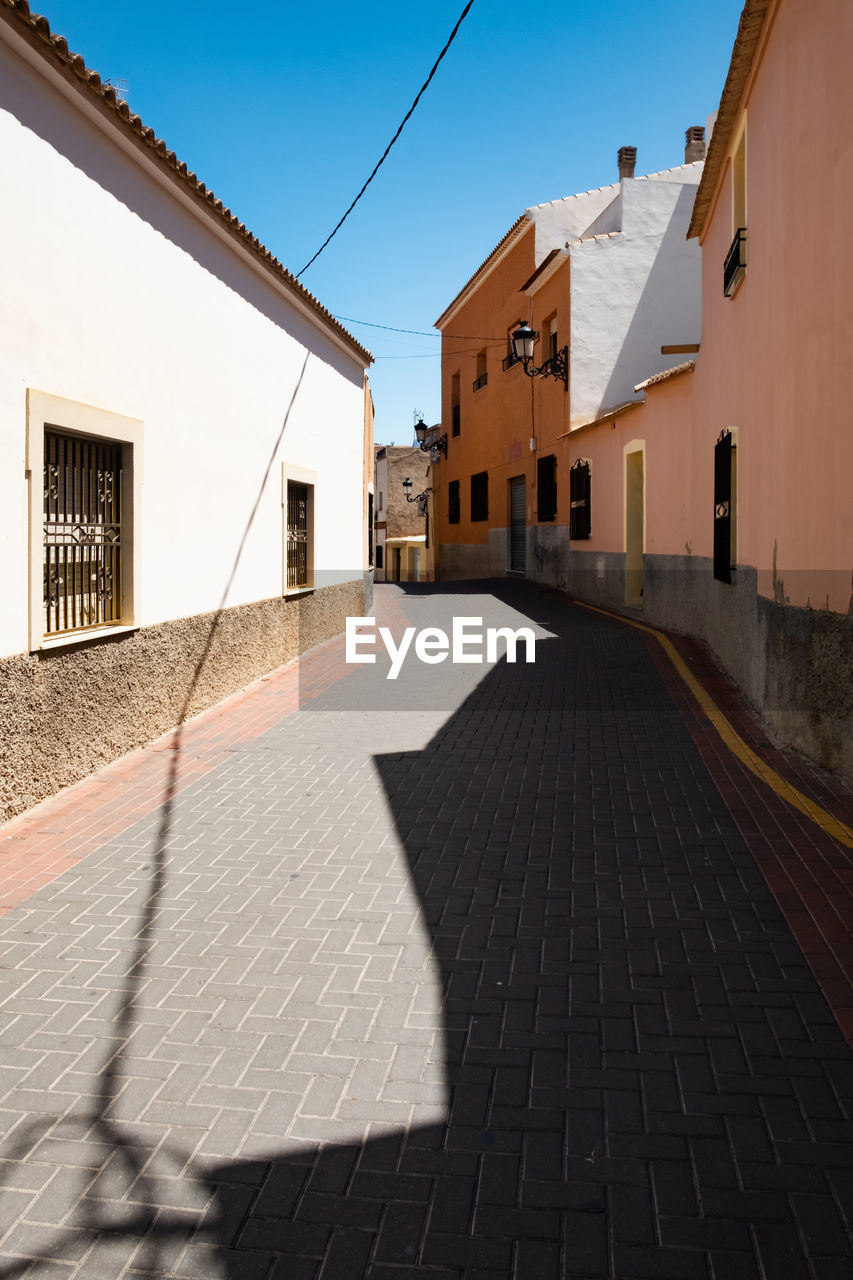 architecture, built structure, building exterior, building, city, street, shadow, sunlight, residential district, nature, house, direction, day, sky, the way forward, no people, footpath, transportation, outdoors, sunny, diminishing perspective, paving stone, alley, long
