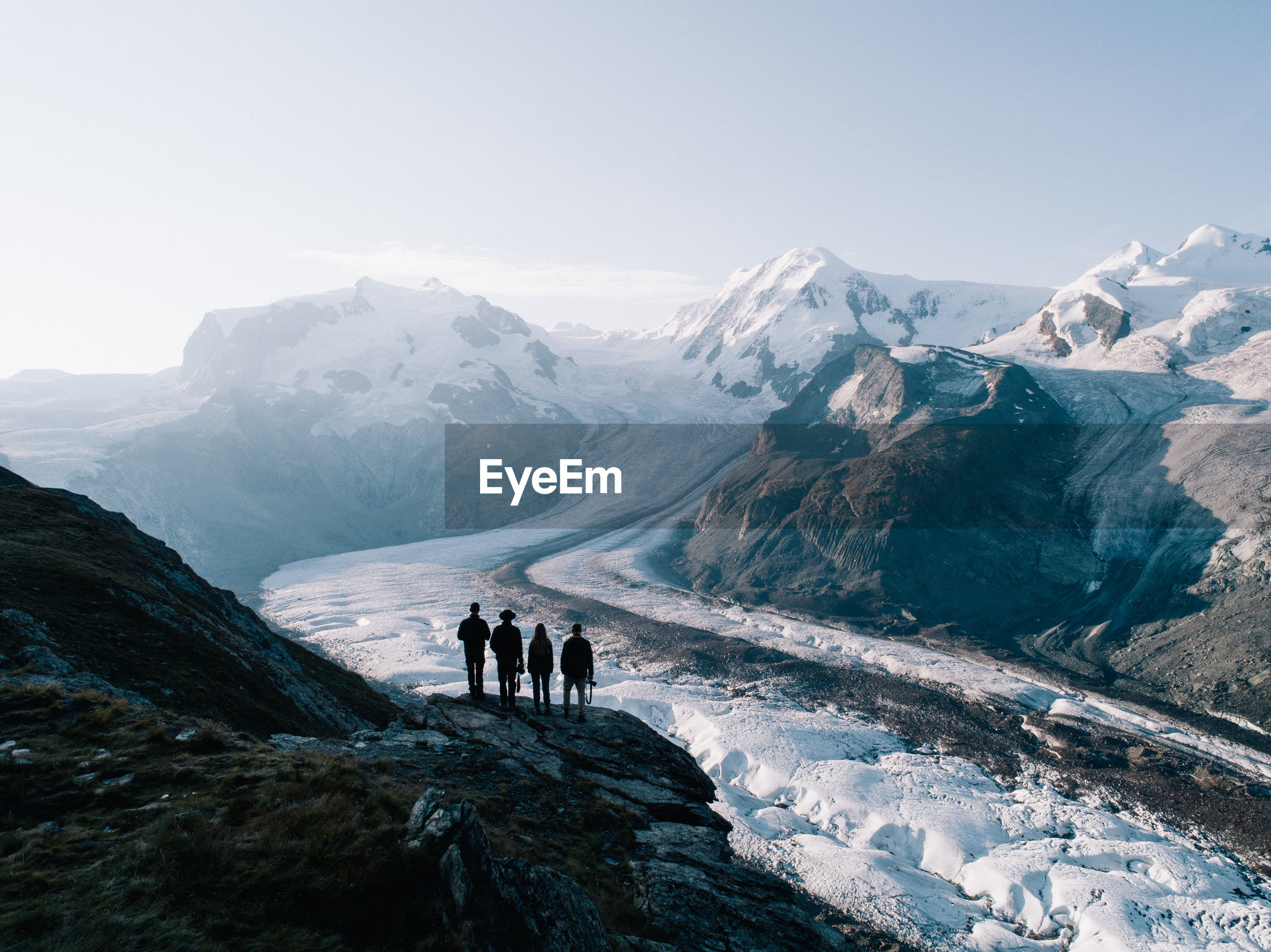 People standing against snowcapped mountain