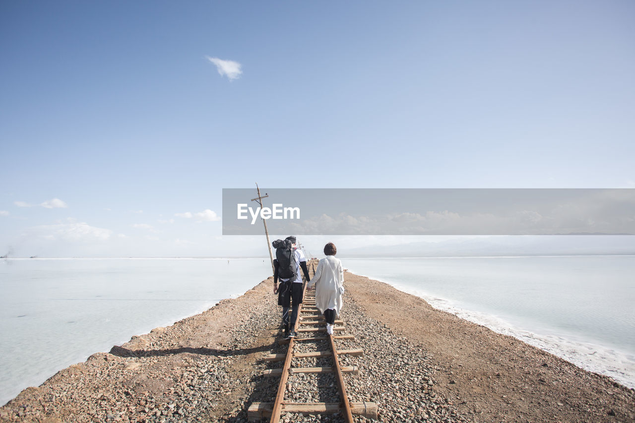 Rear view of couple walking on railroad track against sky