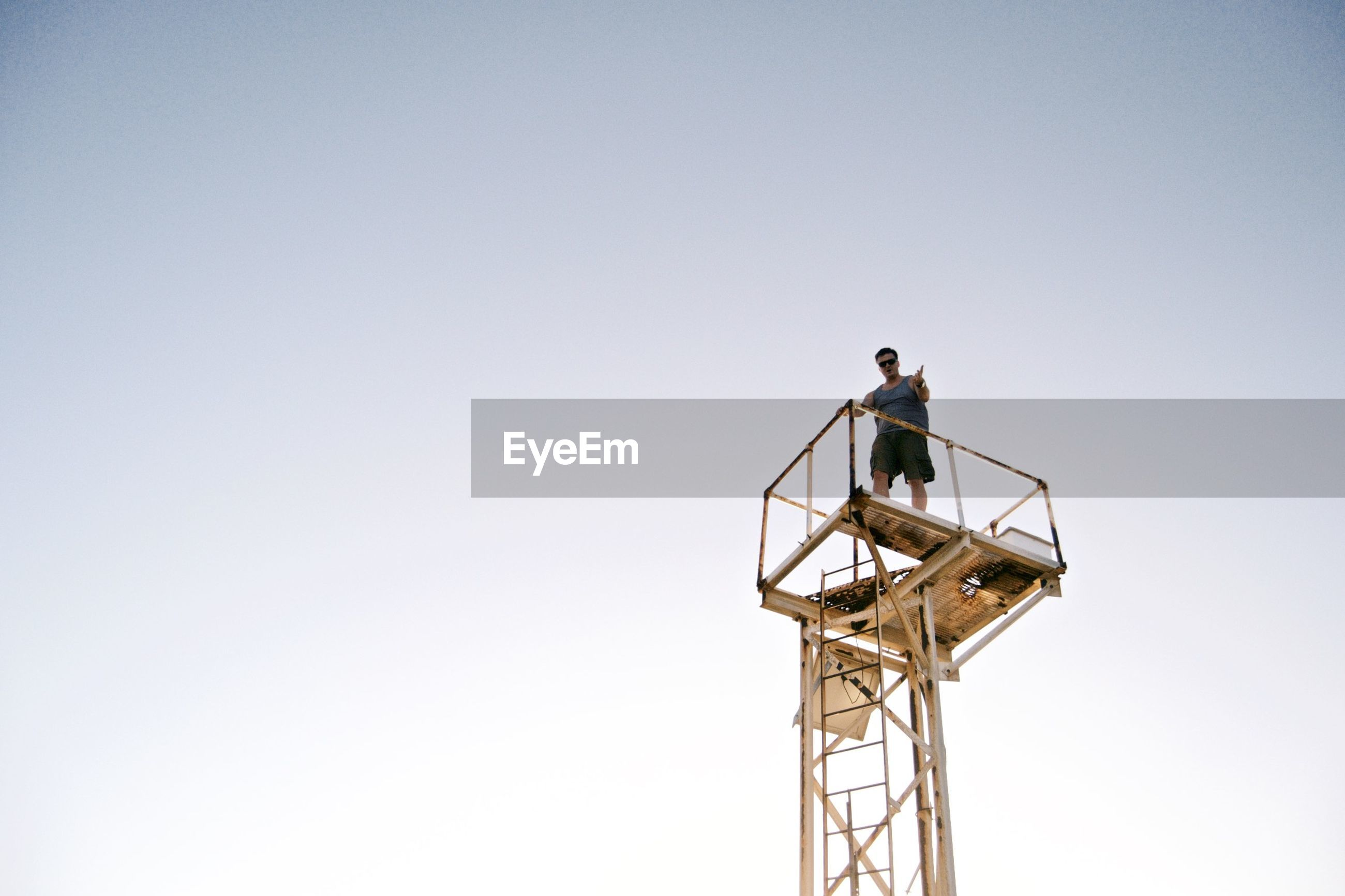 Low angle view of male hiker standing on observation point against clear sky