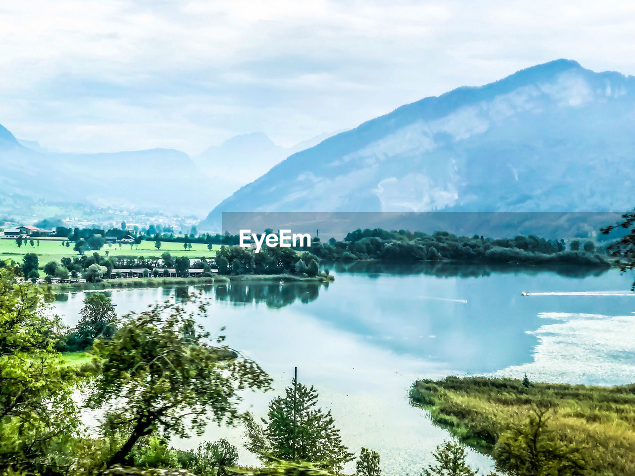 water, sky, beauty in nature, cloud - sky, scenics - nature, lake, tranquil scene, reflection, tree, tranquility, mountain, plant, nature, day, green color, no people, non-urban scene, idyllic, mountain range