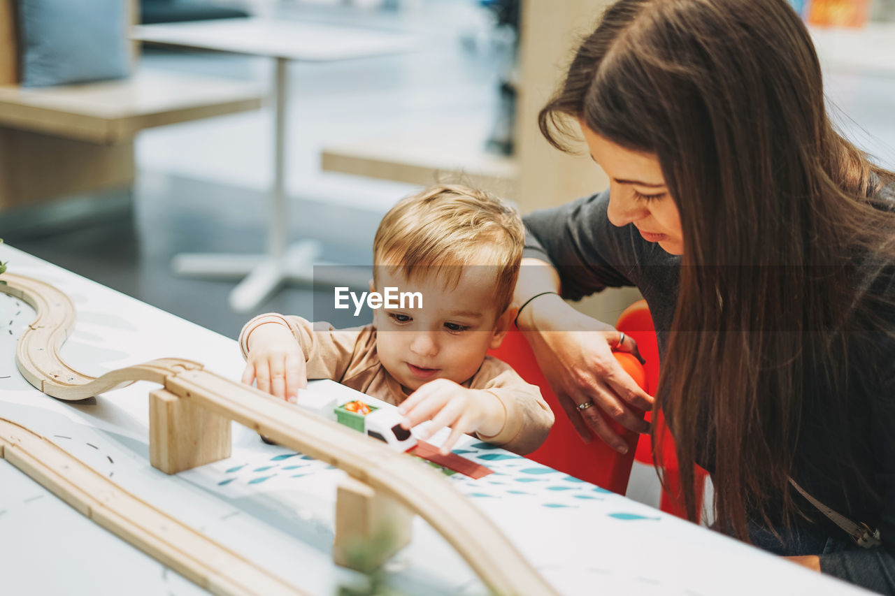 High angle view of woman looking at son playing with toy