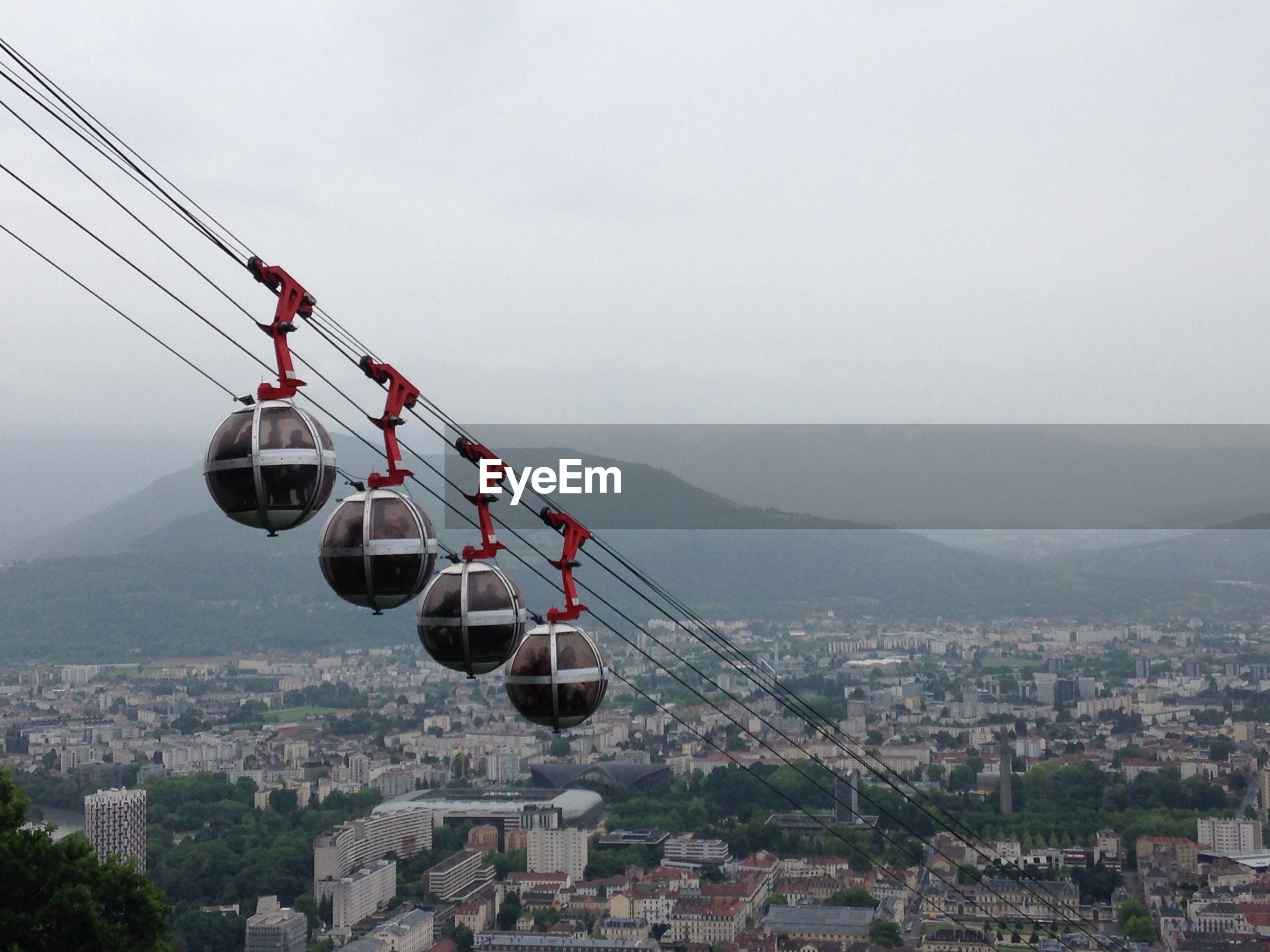 View of overhead cable cars in city against sky