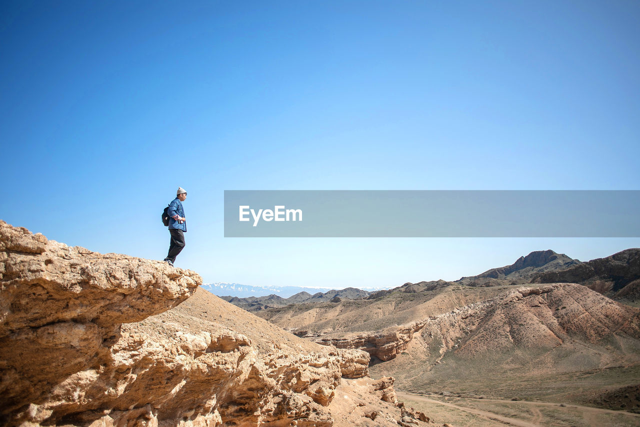 clear sky, sky, rock, one person, leisure activity, real people, rock - object, solid, beauty in nature, mountain, blue, lifestyles, scenics - nature, nature, copy space, tranquility, tranquil scene, day, non-urban scene, mountain range, outdoors, human arm