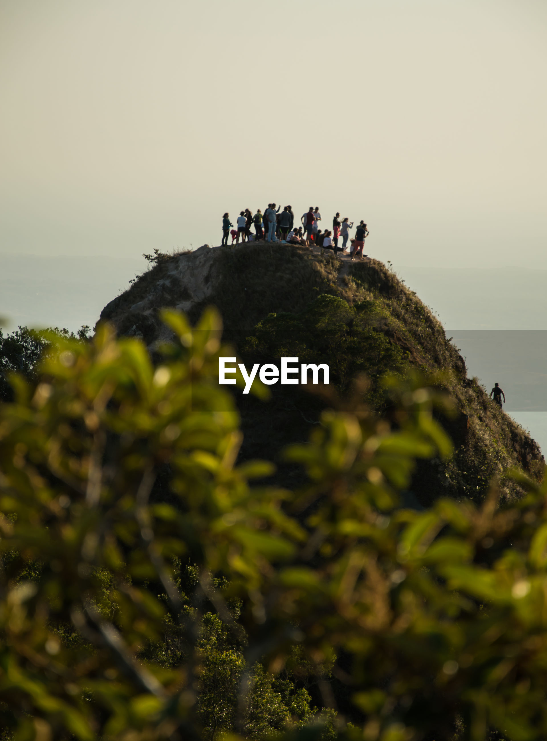 Low angle view of people standing on cliff against sky