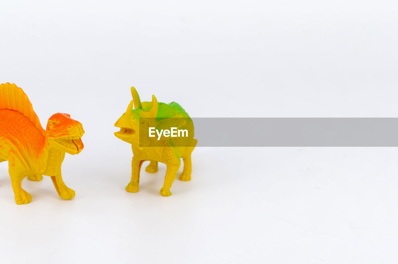 animal representation, white background, copy space, representation, animal, studio shot, animal themes, indoors, toy, mammal, yellow, still life, livestock, no people, art and craft, domestic animals, toy animal, single object, creativity, cut out