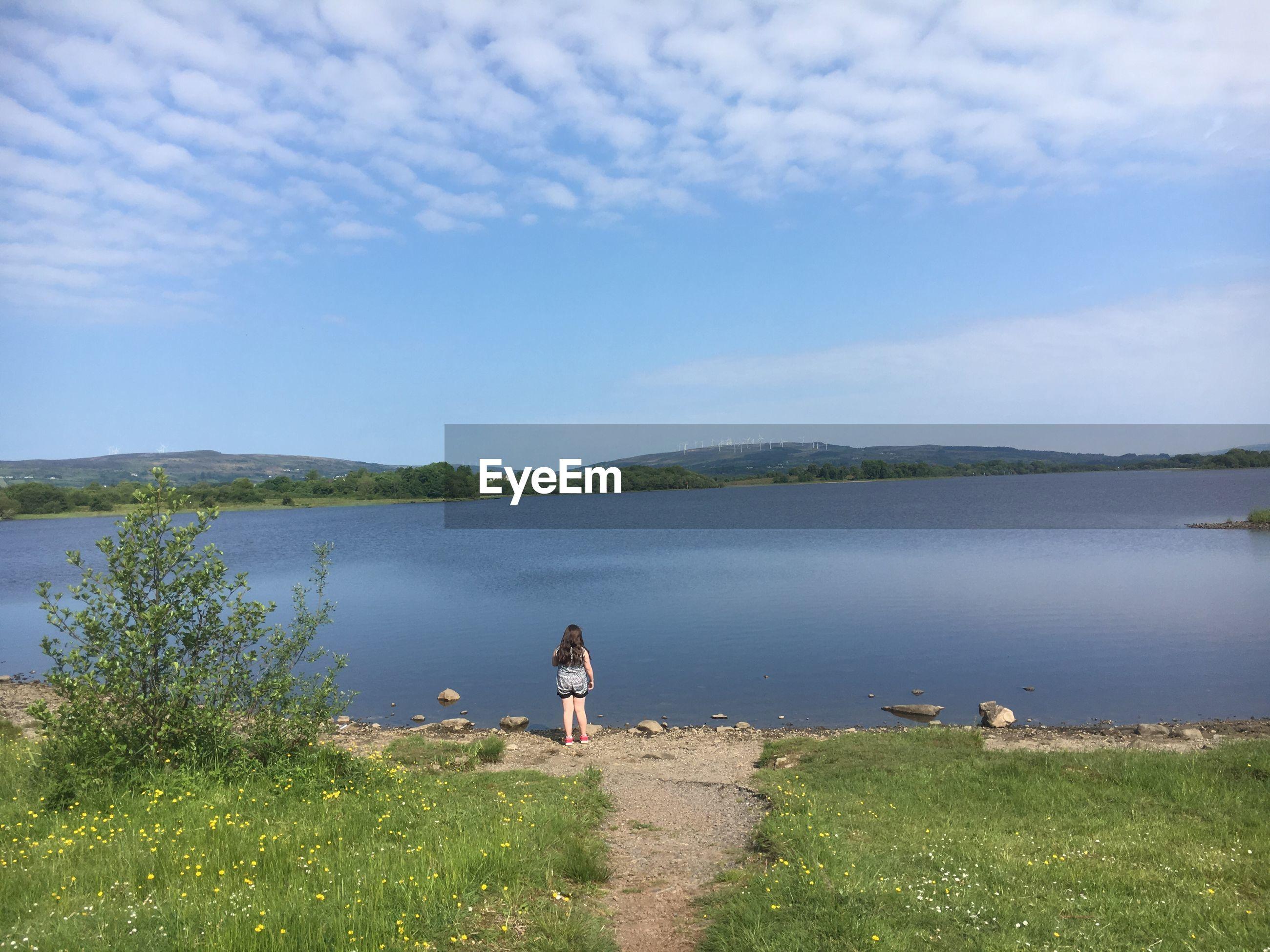 Rear view of girl walking at lakeshore against sky