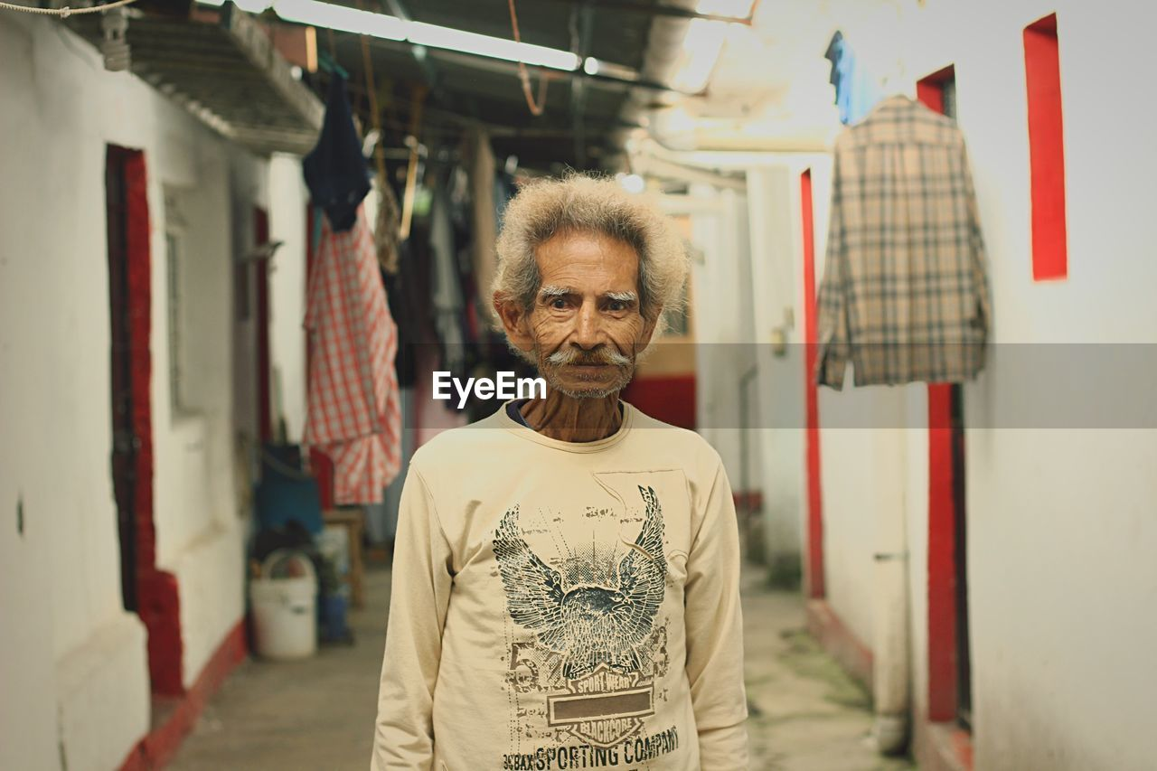 Portrait of senior man standing in alley