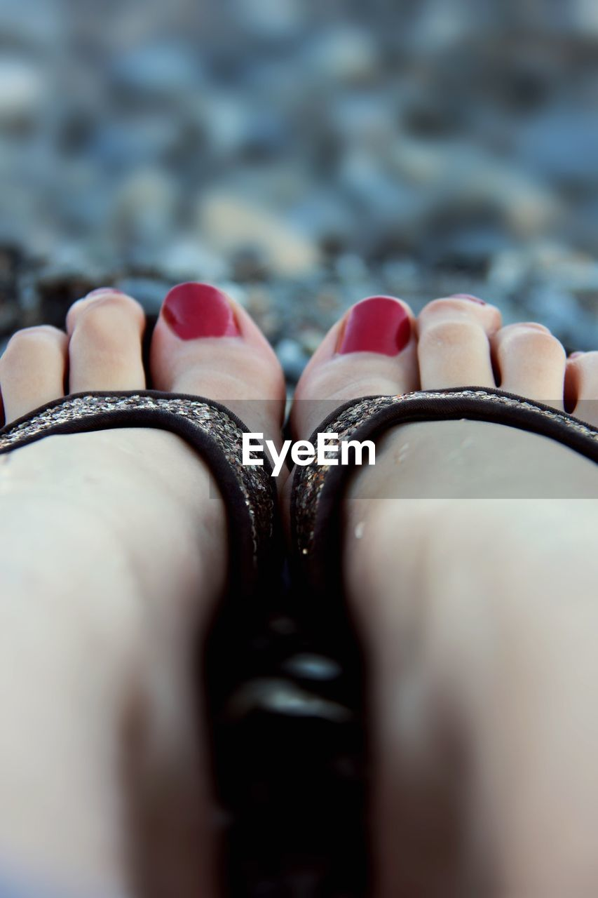 Low Section Of Woman With Red Painted Toenails Wearing Sandals