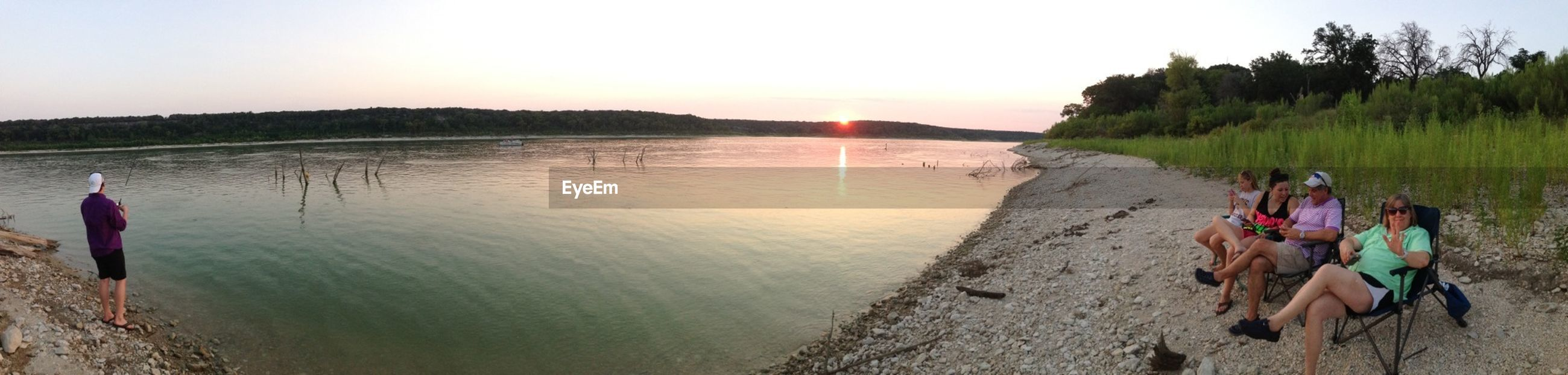 water, tranquil scene, tranquility, scenics, clear sky, beauty in nature, nature, beach, tree, sky, incidental people, sunset, leisure activity, idyllic, sea, lake, sand, shore, sunlight