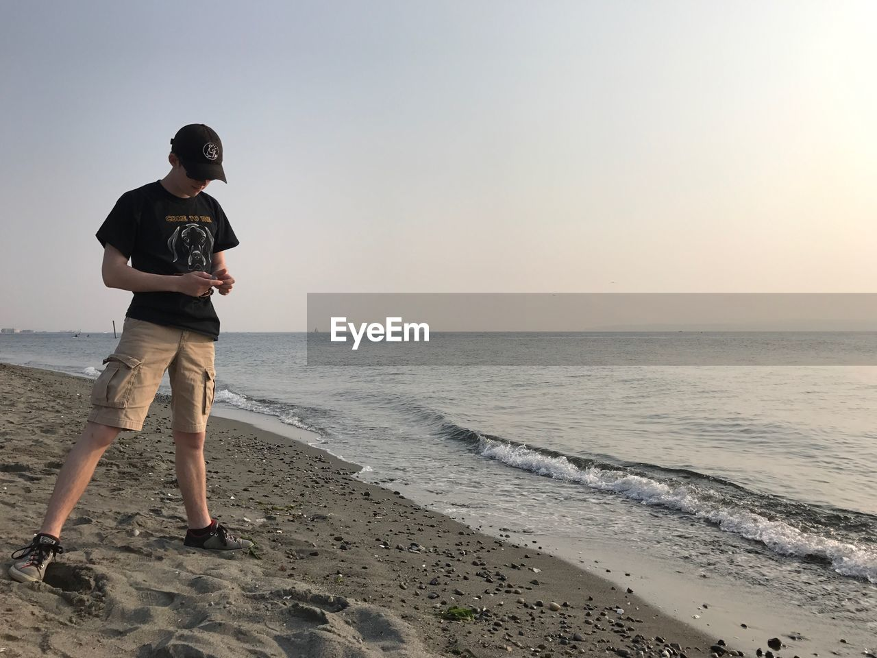 Full length of teenager boy standing at beach against clear sky