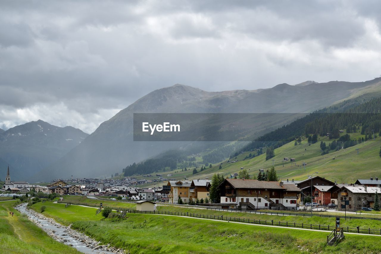 mountain, scenics - nature, cloud - sky, sky, building exterior, architecture, built structure, mountain range, building, environment, house, nature, beauty in nature, landscape, land, non-urban scene, green color, day, plant, grass, no people, outdoors, townscape