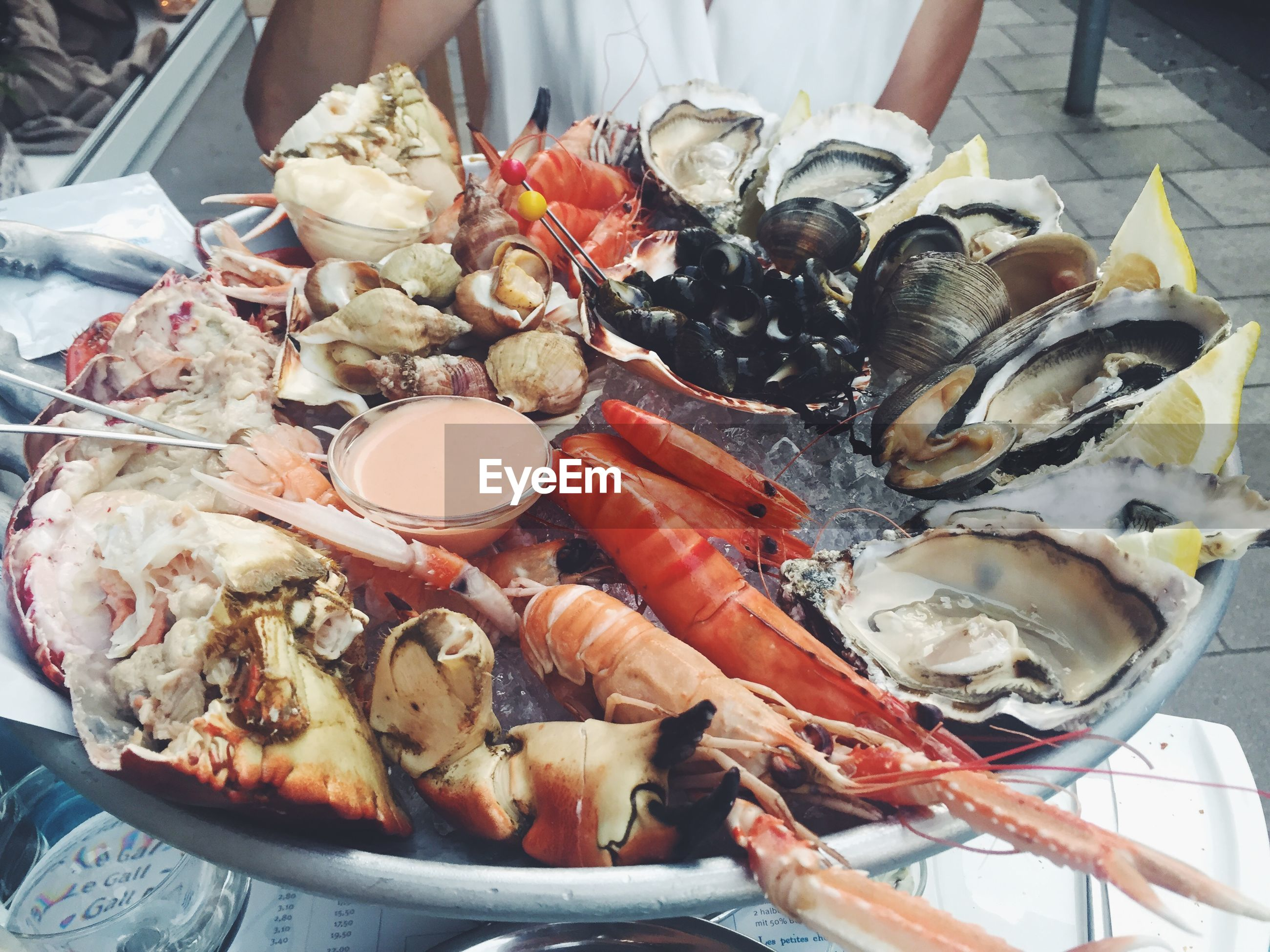 Midsection of woman sitting in front of seafood on plate
