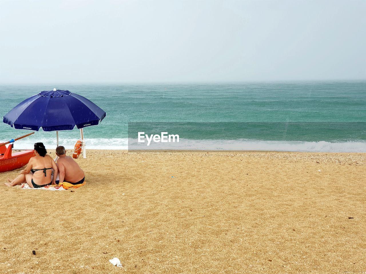 People relaxing on beach against sky