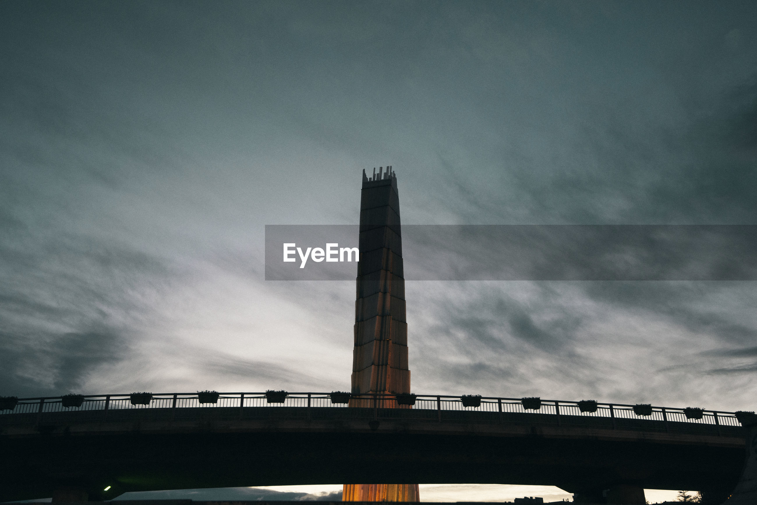 LOW ANGLE VIEW OF BRIDGE AND BUILDING AGAINST SKY AT DUSK