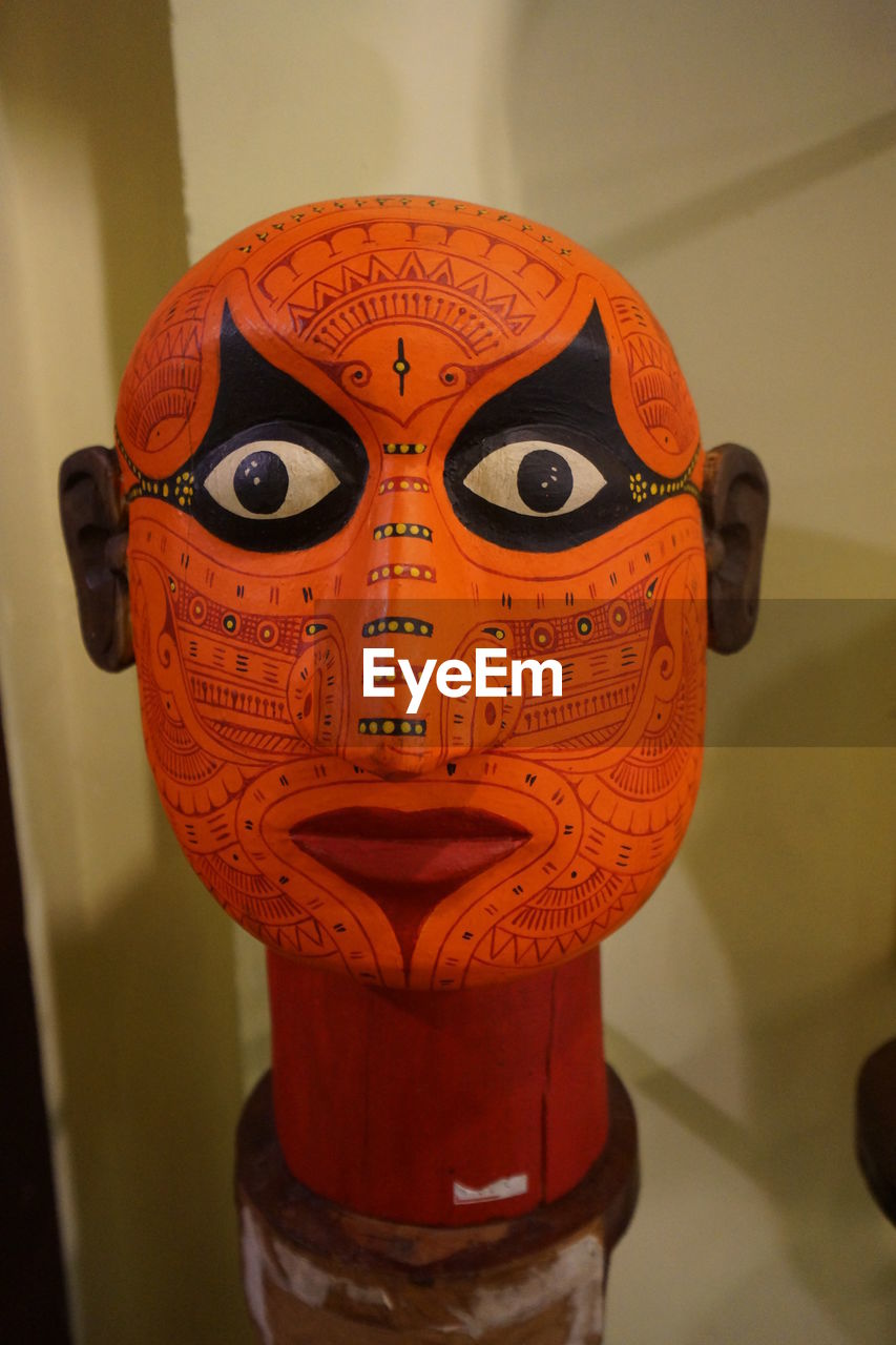 representation, indoors, art and craft, focus on foreground, close-up, no people, human representation, creativity, craft, single object, metal, man made, orange color, man made object, toy, wall - building feature, arts culture and entertainment, male likeness