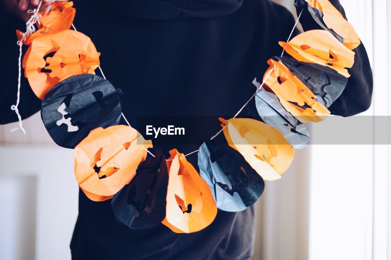 Midsection of person holding halloween decoration at home