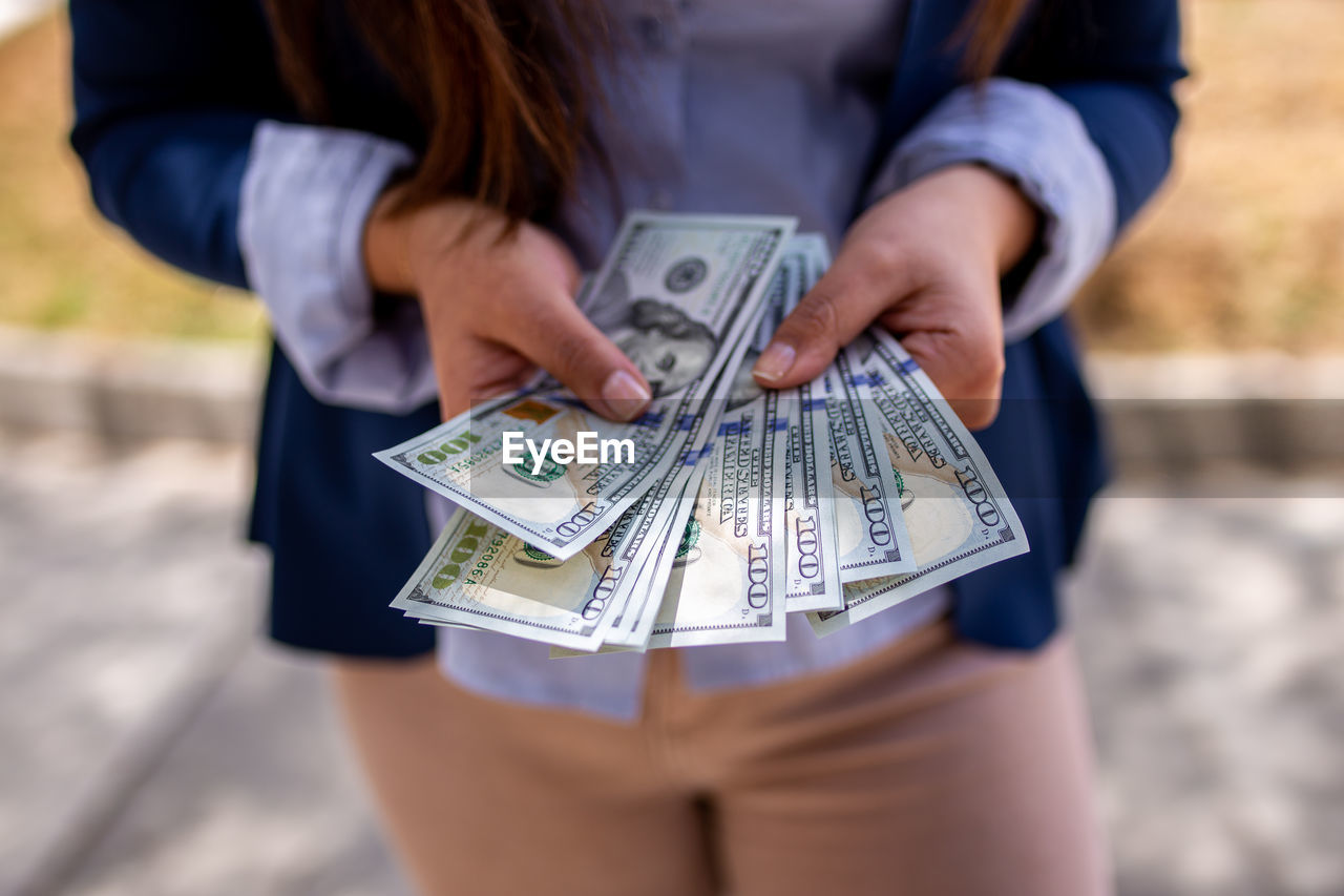 Midsection of woman holding banknotes