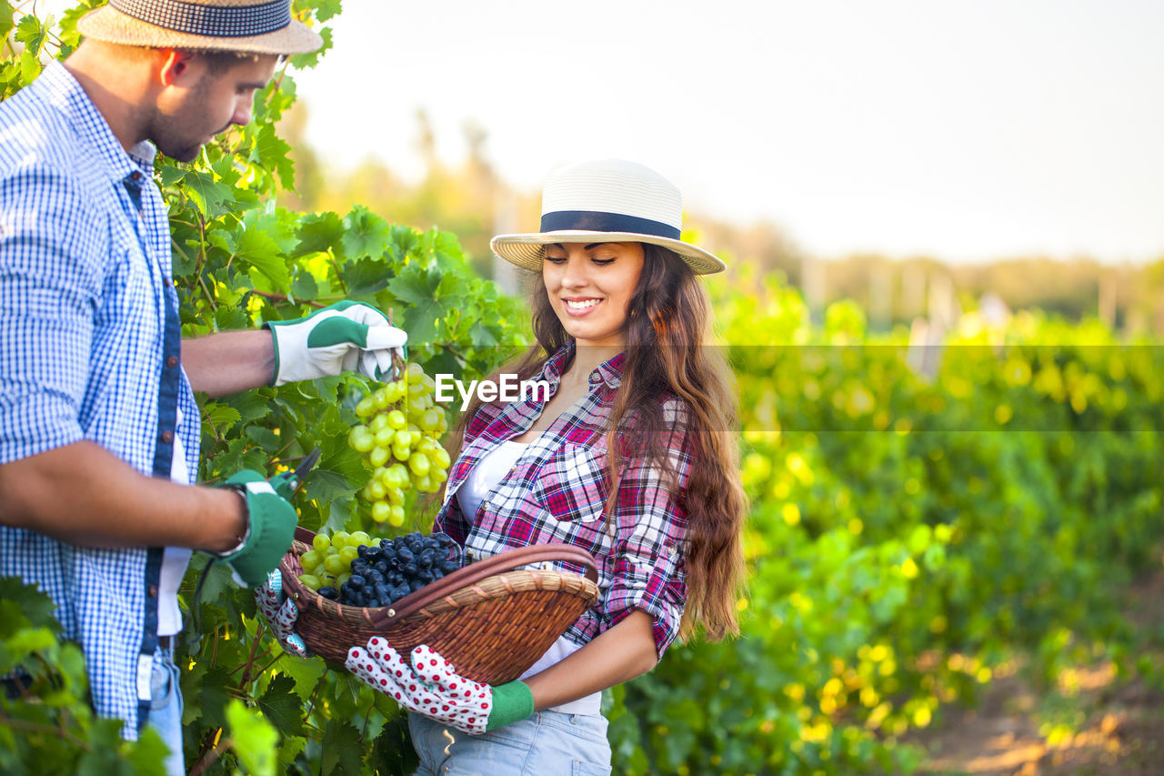 YOUNG WOMAN SMILING WHILE STANDING IN FARM