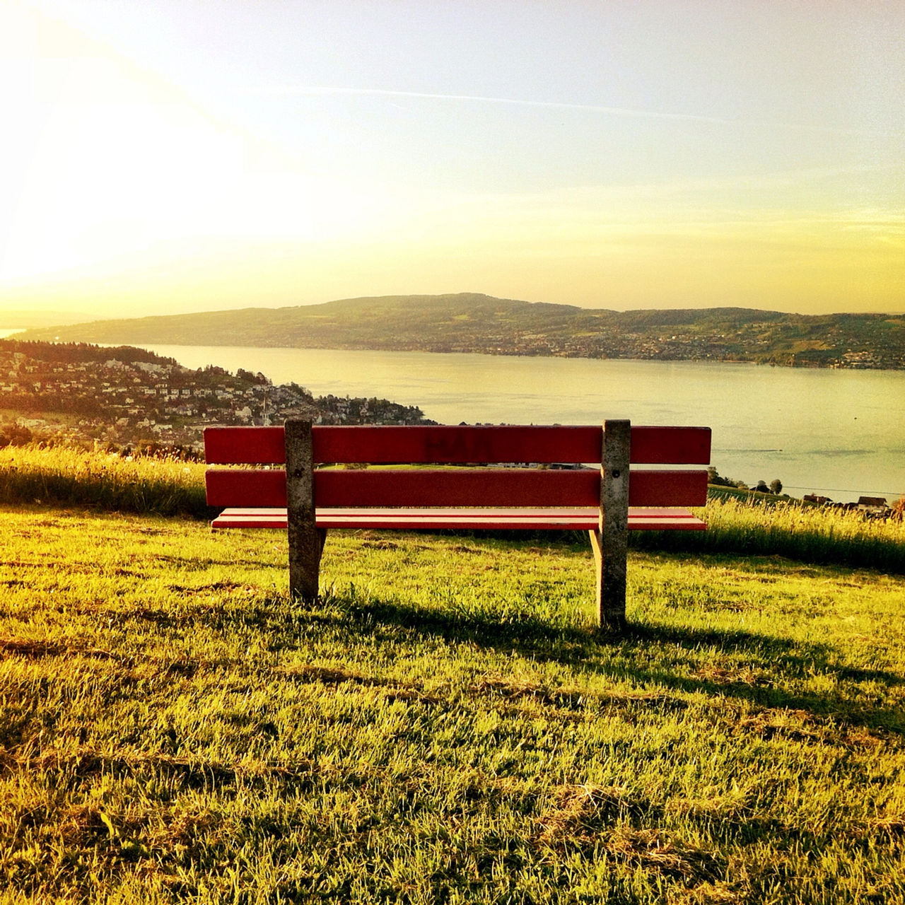 Empty bench on grassy field against lake and sky