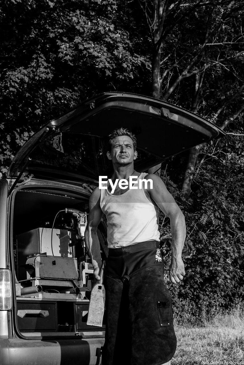 Man Standing Against Car