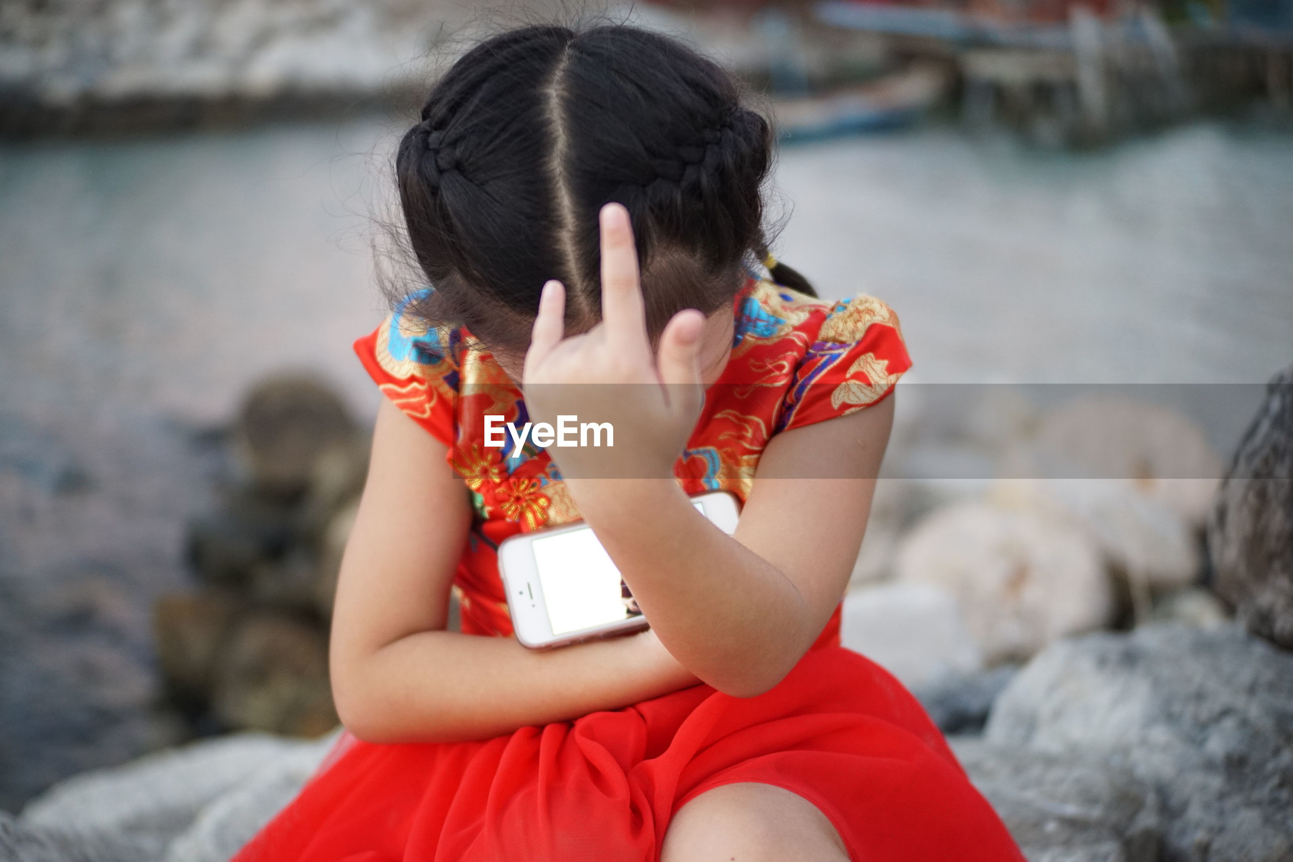 Girl gesturing over mobile phone while sitting on rock against sea